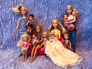 A picture of 11 Barbie Dolls against a purple background for a Barbie Doll Story.  It's set up like a family portrait.  3 Actual Barbie Dolls, 1 Stacie, 3 Chelsea Dolls, 2 toddler dolls and 2 baby dolls.