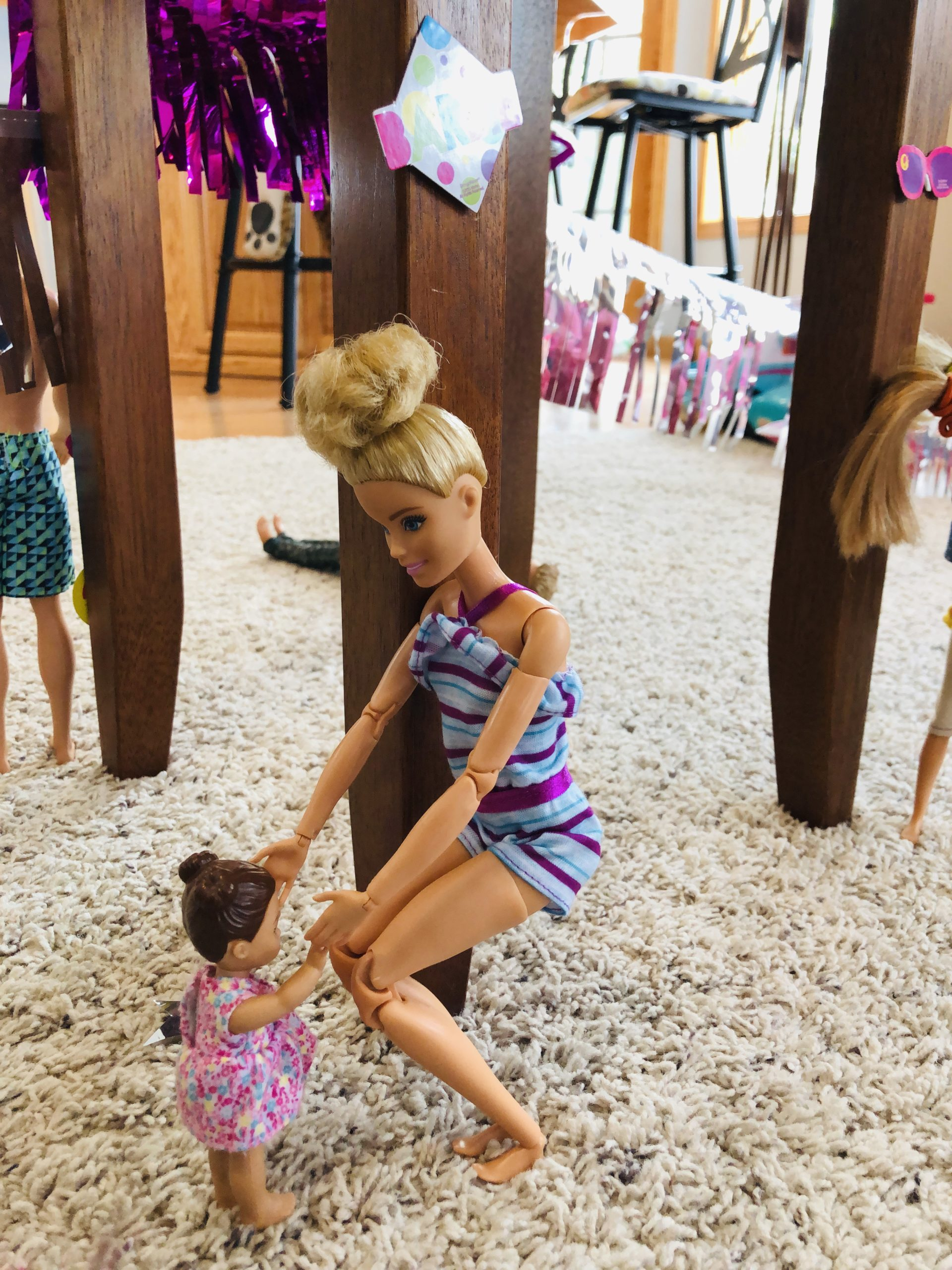 Barbie is holding hands and dancing with a smaller Barbie doll.