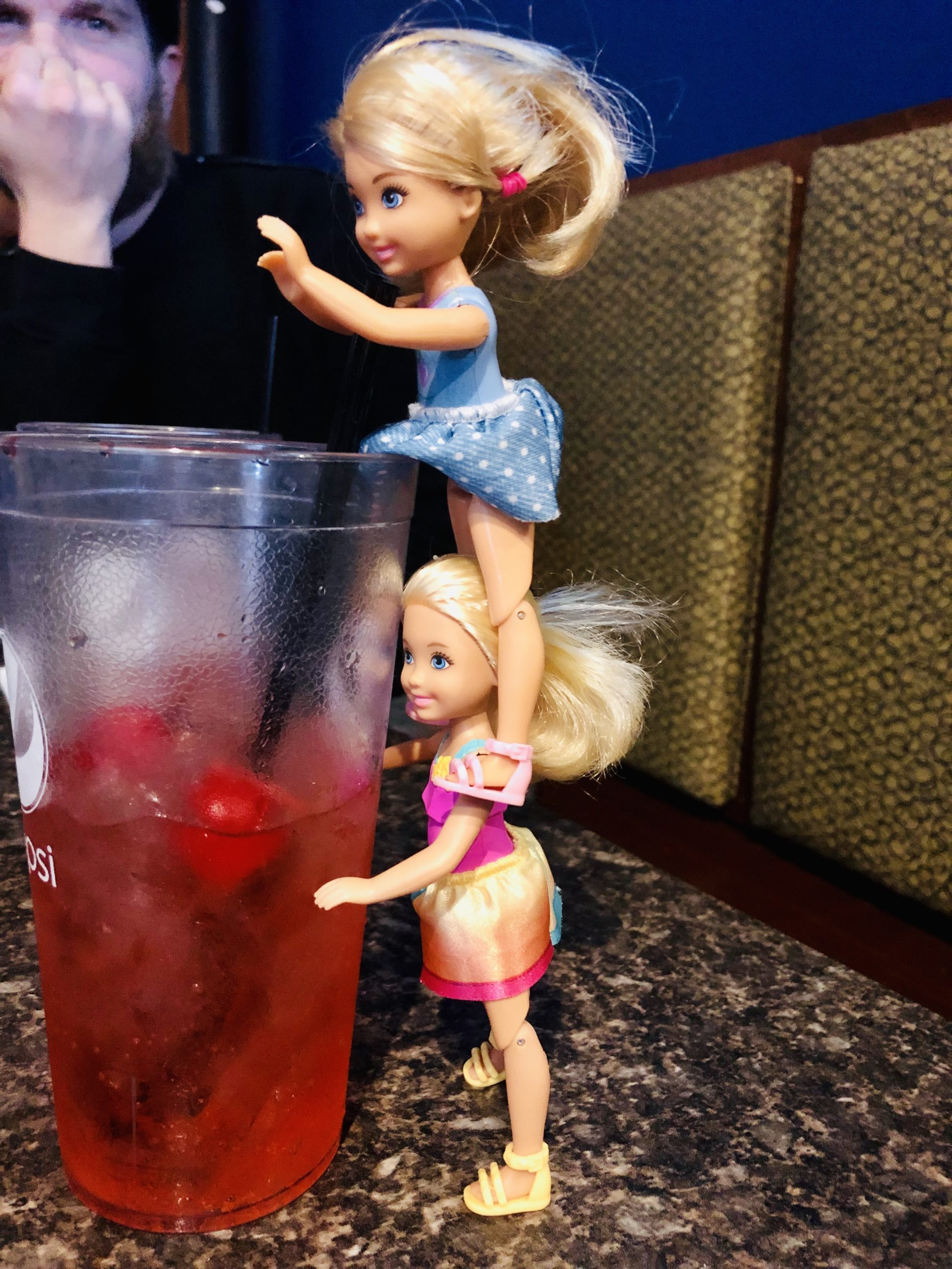 A Chelsea Doll Brynn, blue dress, is standing on another Chelsea doll's (Rowan) shoulders.