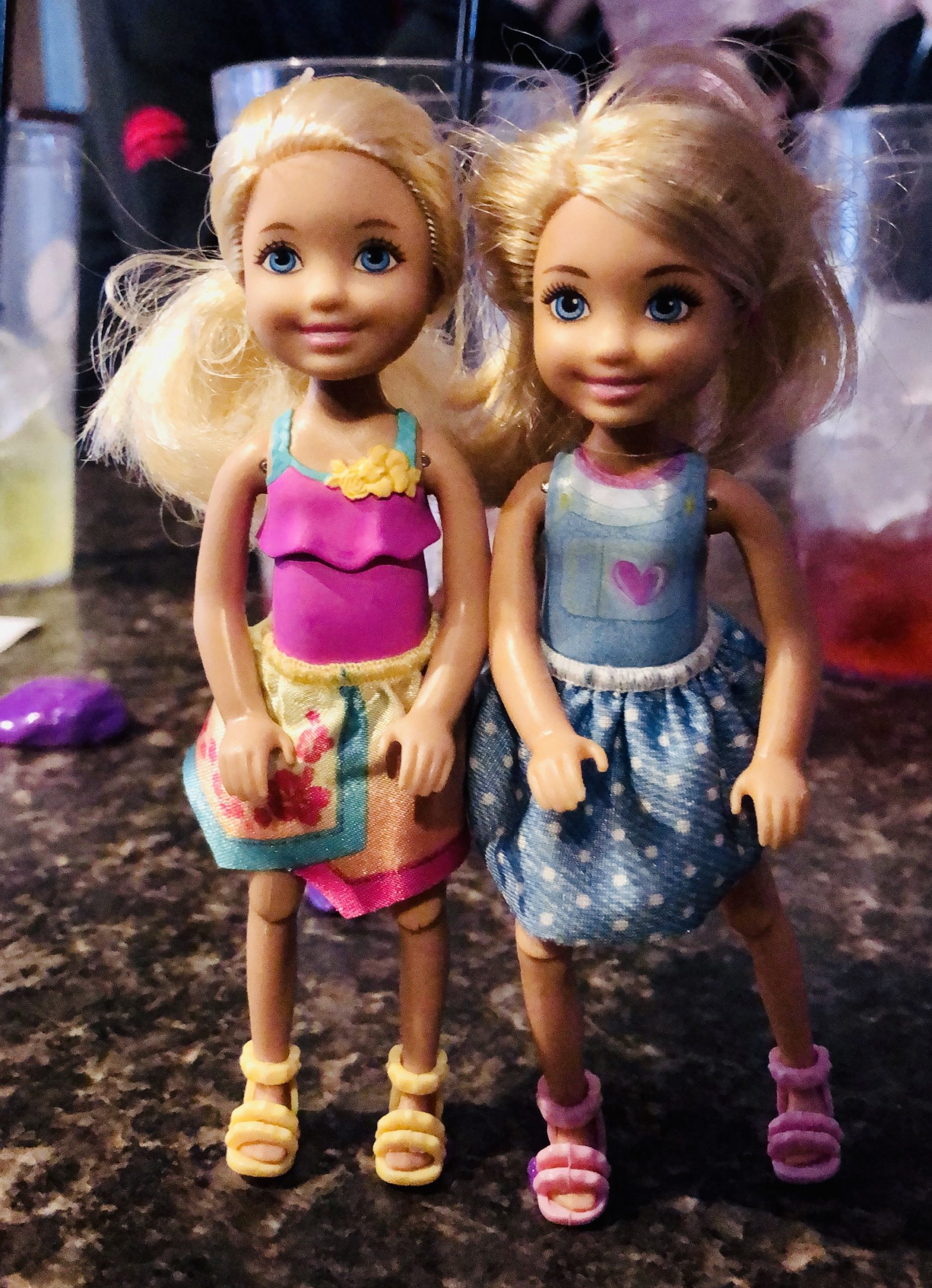 2 blonde haired Chelsea dolls named Brynn and Rowan for the short story Rowan's Diary.  One  is wearing a pink dress and the other has a blue dress on.