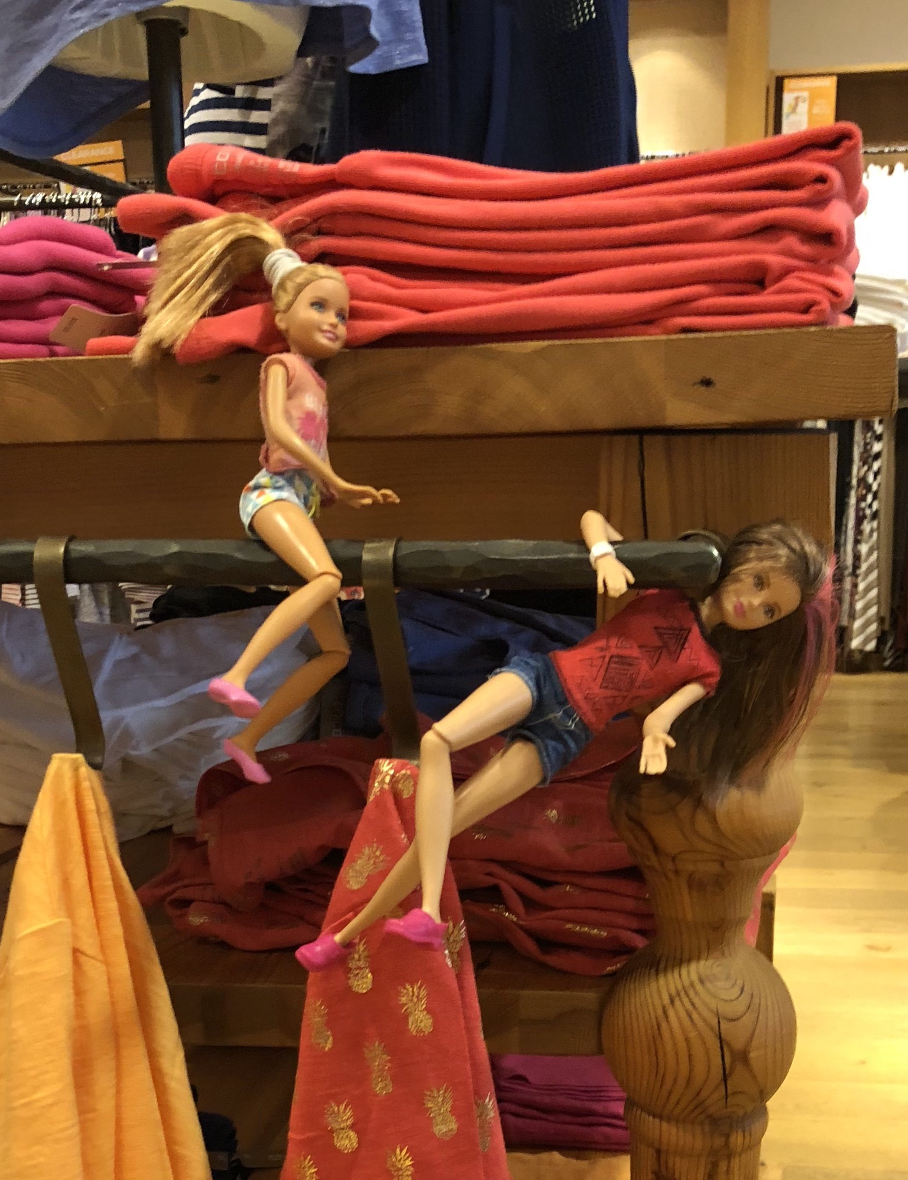 2 Barbie Dolls hanging on some hooks in a clothing store for the Barbie Doll Story, Shopping Fails.