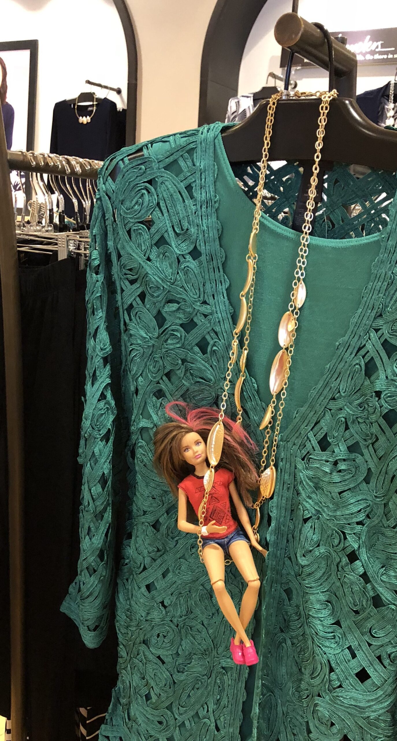 Skipper doll hanging on a necklace, for the Barbie Doll Story Shopping Fails.