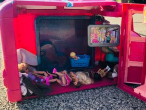 Barbies laying all over the pink Barbie Camper for the Barbie doll Story, Trekking to School.