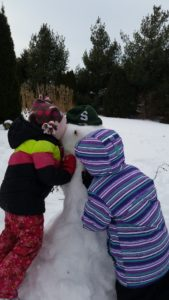 2 girls kissing a snowman for the snowman story, The Special Snowman.