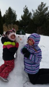 2 girls standing by a snowman for the snowman story, The Special Snowman.