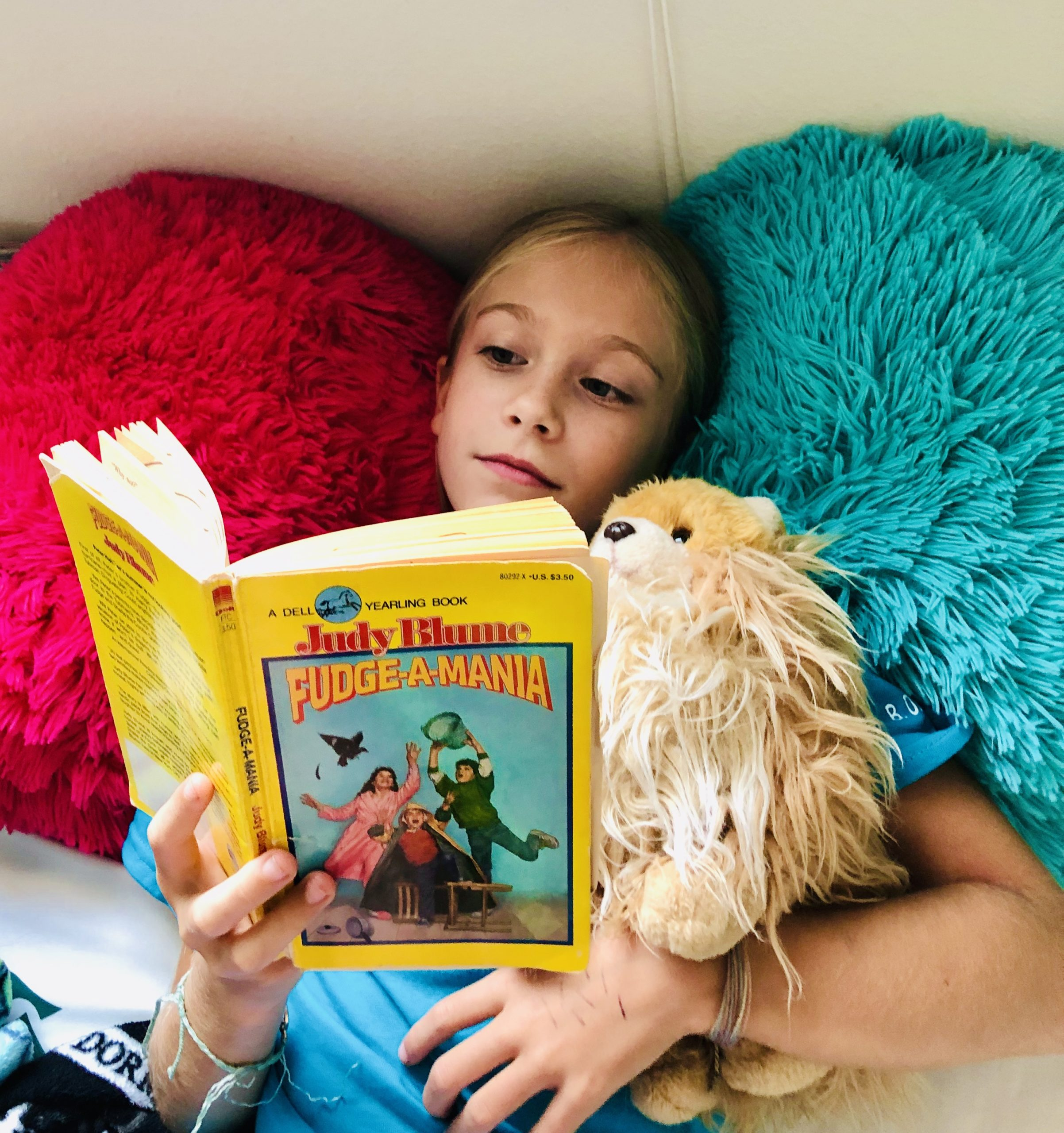 For the book review, a blond haired girl, Brecken, reading Fudge-A-Mania by Judy Blume. She's laying on 2 fuzzy pillows, hot pink and blue.