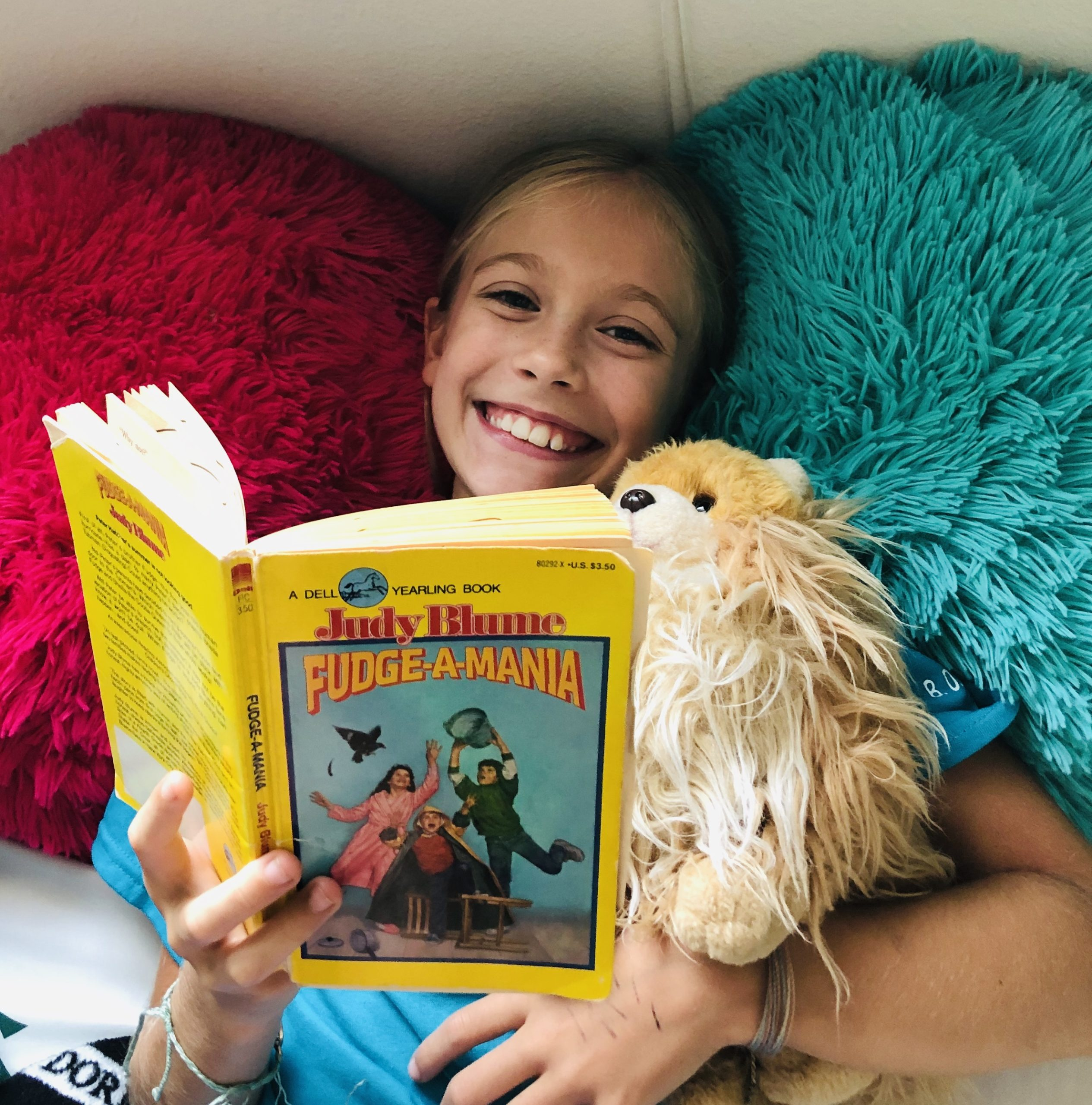 For the book review, a blond haired girl, Brecken, reading Fudge-A-Mania by Judy Blume. She's laying on 2 fuzzy pillows, hot pink and blue. She's smiling.