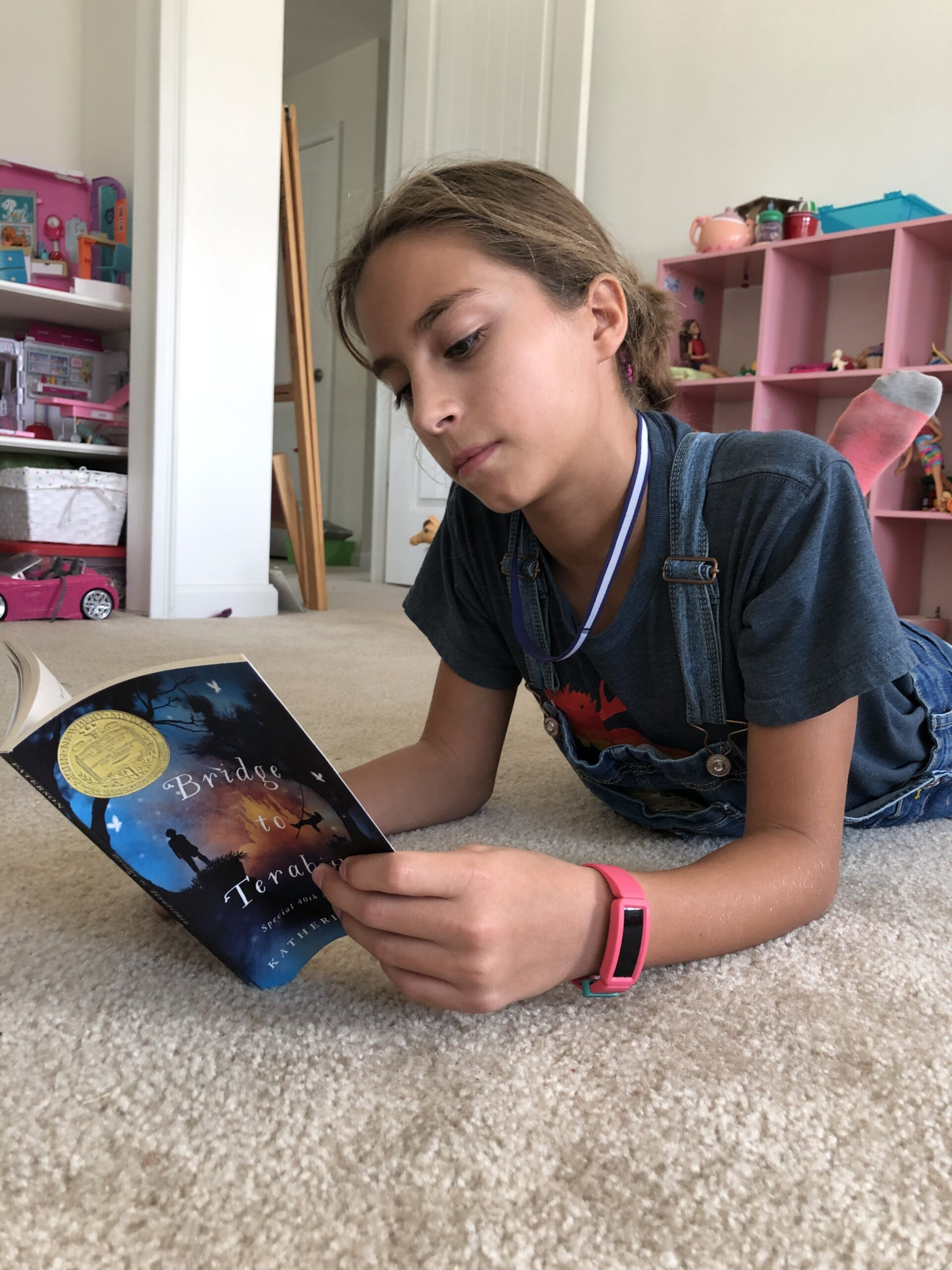 Girl reading Bridge to Terabithia for the children's book review.