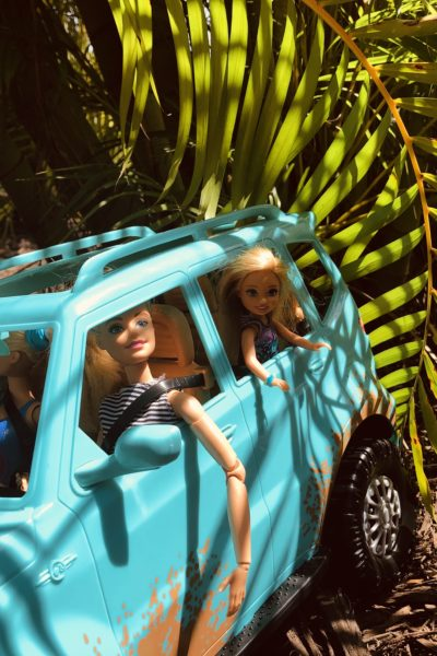 Side of a teal Barbie Jeep with Barbie and a Chelsea looking out of the window at the scenery of a jungle.