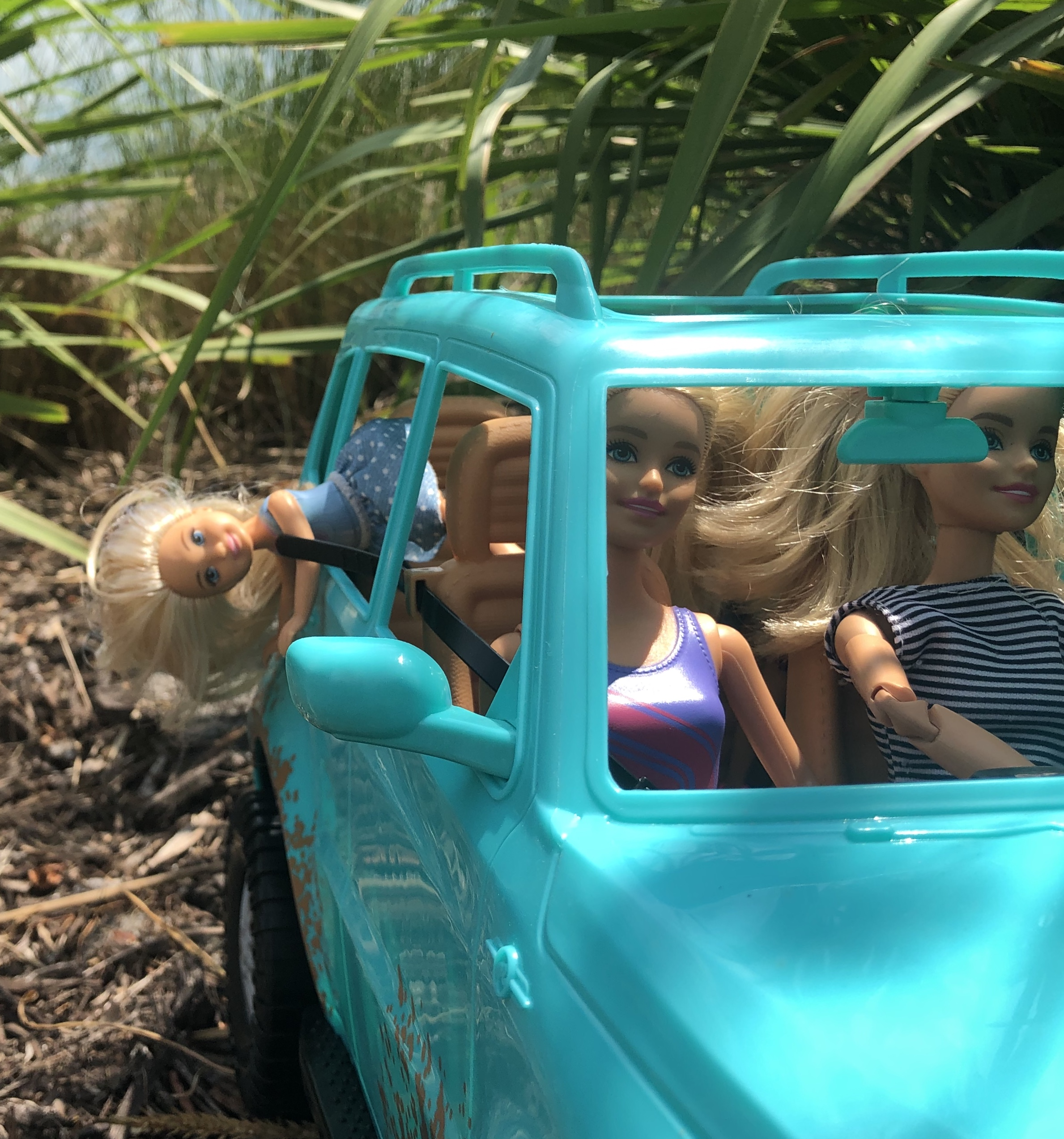 A Chelsea doll falling out the backseat of a teal Jeep. Her head and upper body is hanging down.