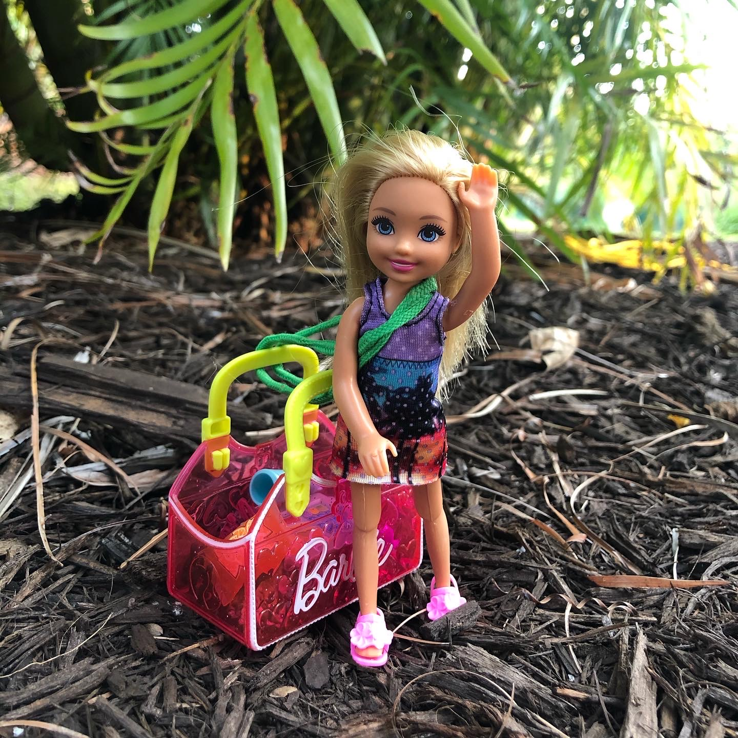 A Chelsea doll waving at the camera with a pink Barbie bag next to her for the Barbie story for kids, Hiking in Costa Rica.
