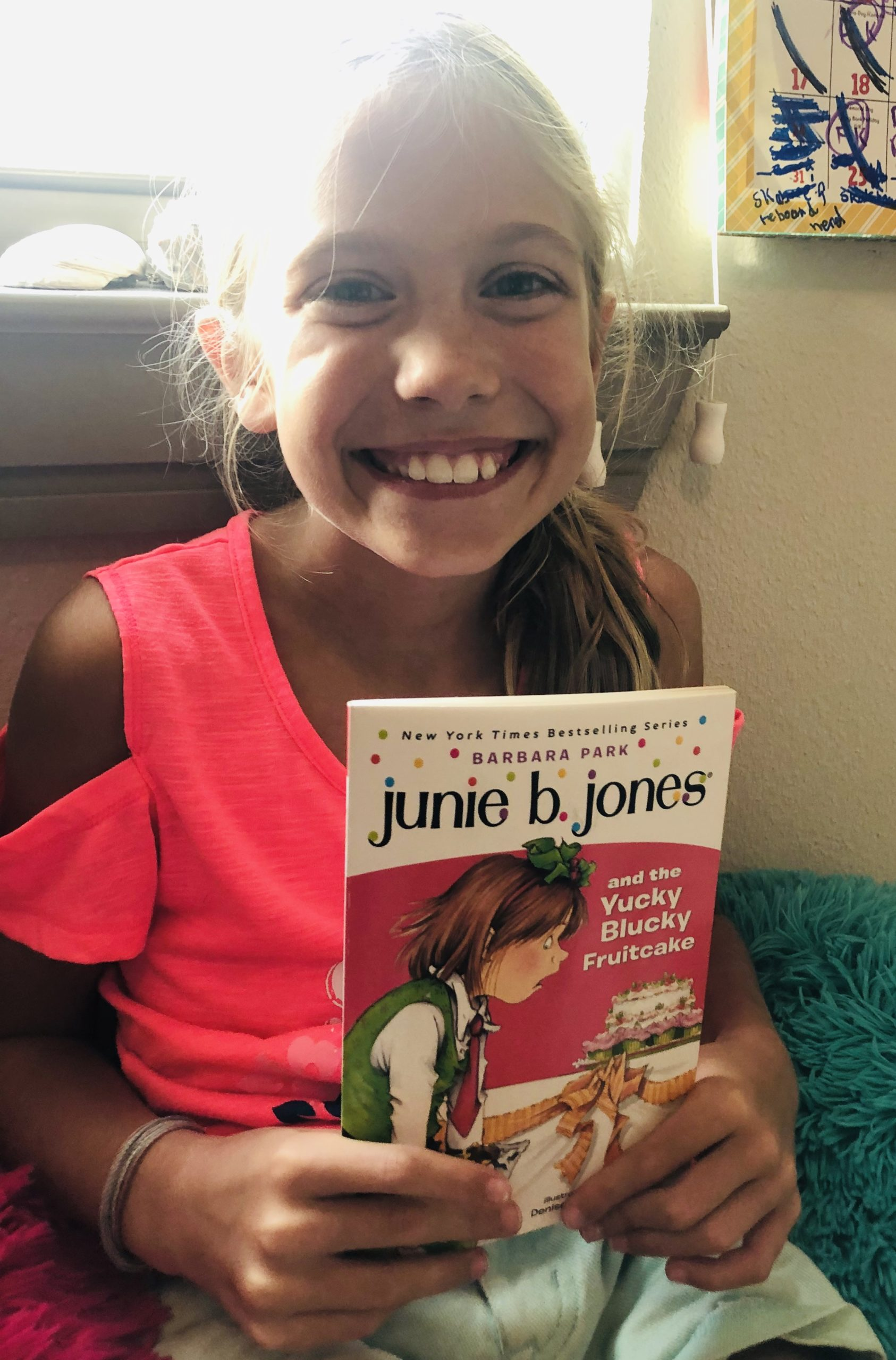 Blonde haired girl smiling at camera holding the book, Junie B. Jones and the Yucky Blucky Fruitcake for the children's book review by K and B Life.