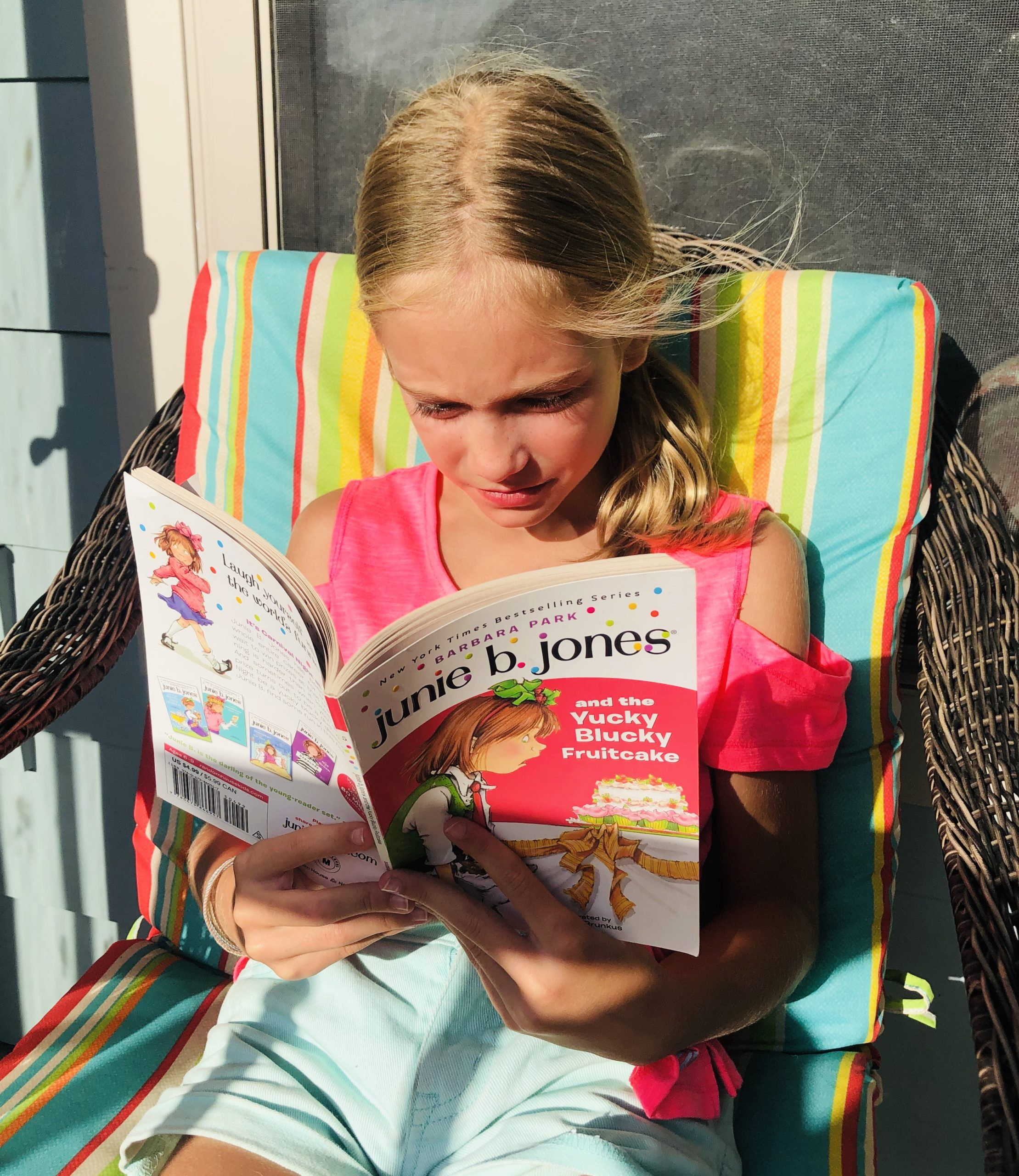 Blonde haired girl reading the book, Junie B. Jones and the Yucky Blucky Fruitcake for the children's book review.