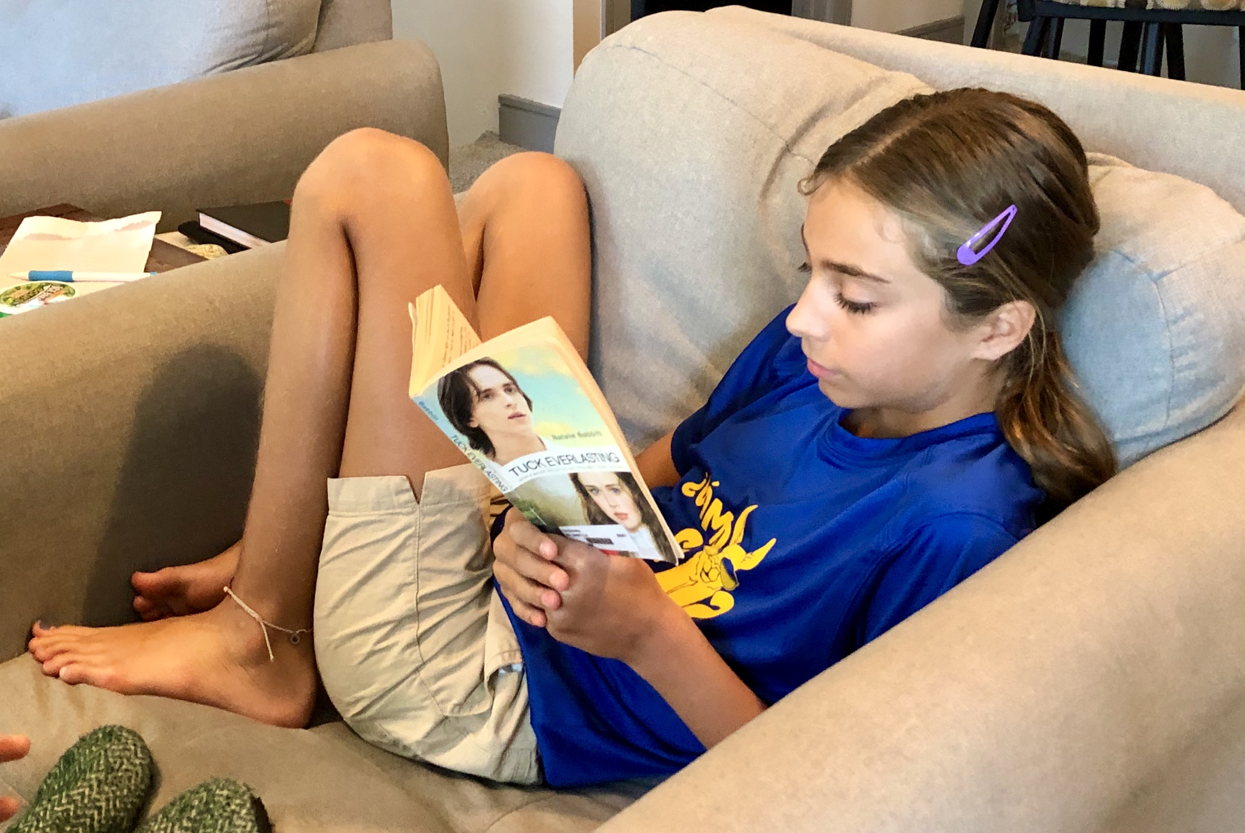 A young girl with her head down reading Tuck Everlasting by Natalie Babbitt for a children's Book Review by Kandblife.com