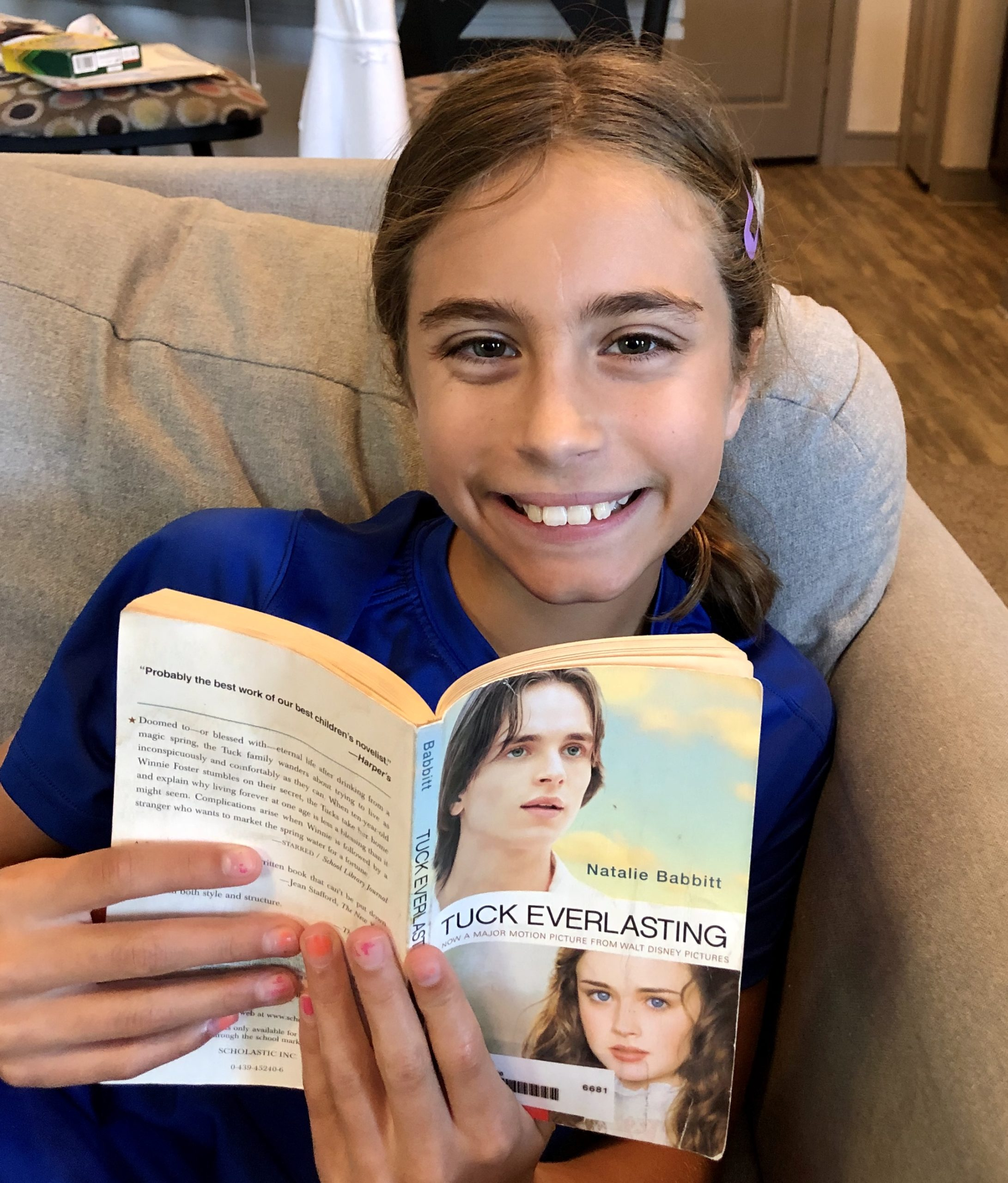 A young girl smiling at the camera, while holding the book Tuck Everlasting by Natalie Babbitt for a children's Book Review by Kandblife.com