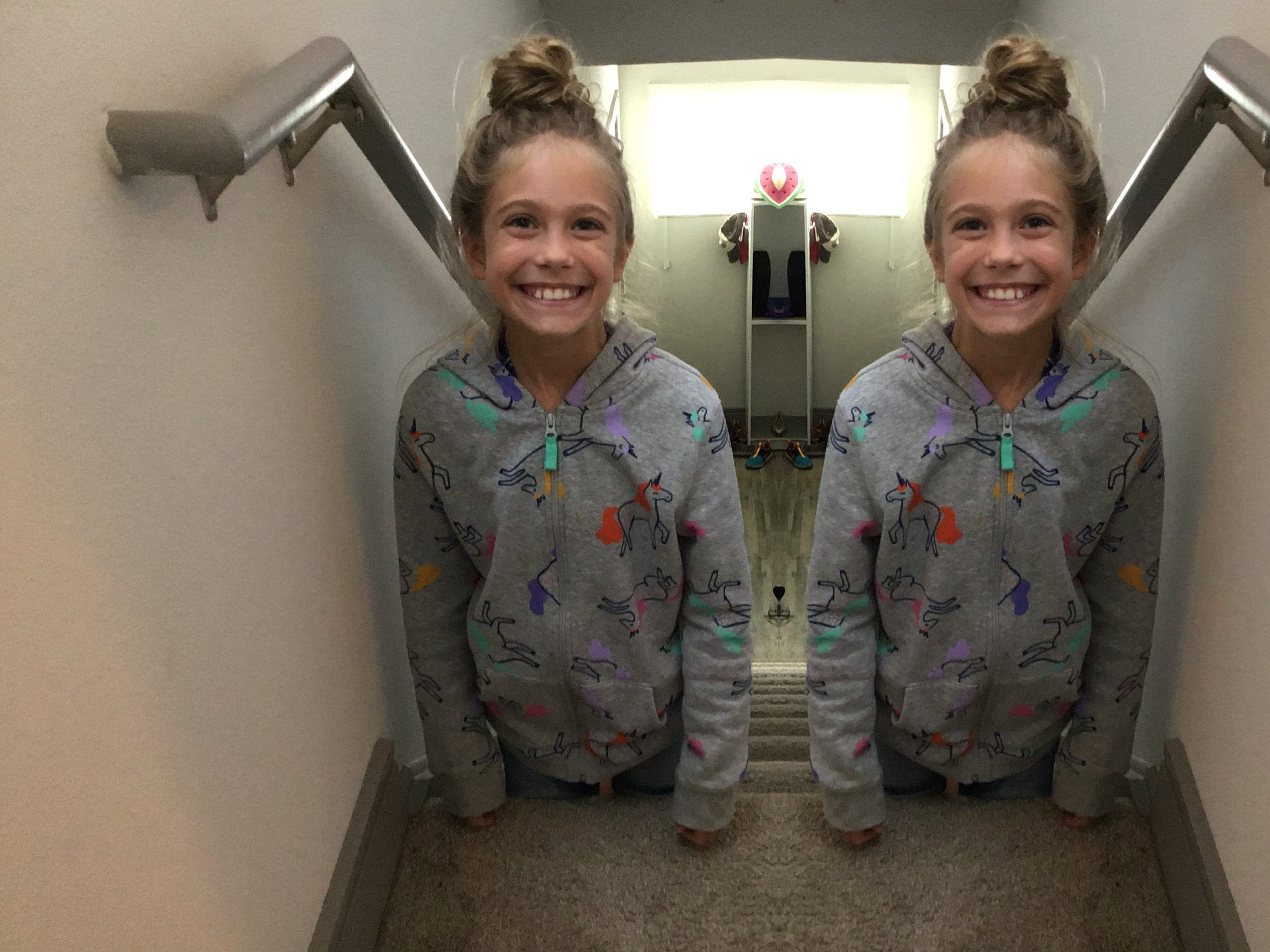 A mirror image of a little blonde girl.