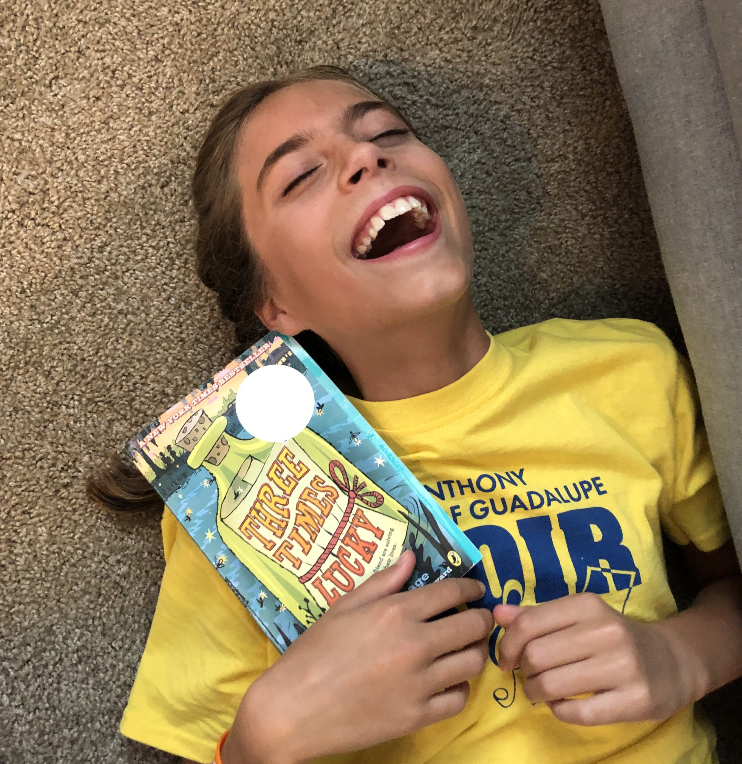 Girl with brown pigtails laughing holding the book Three Times Lucky