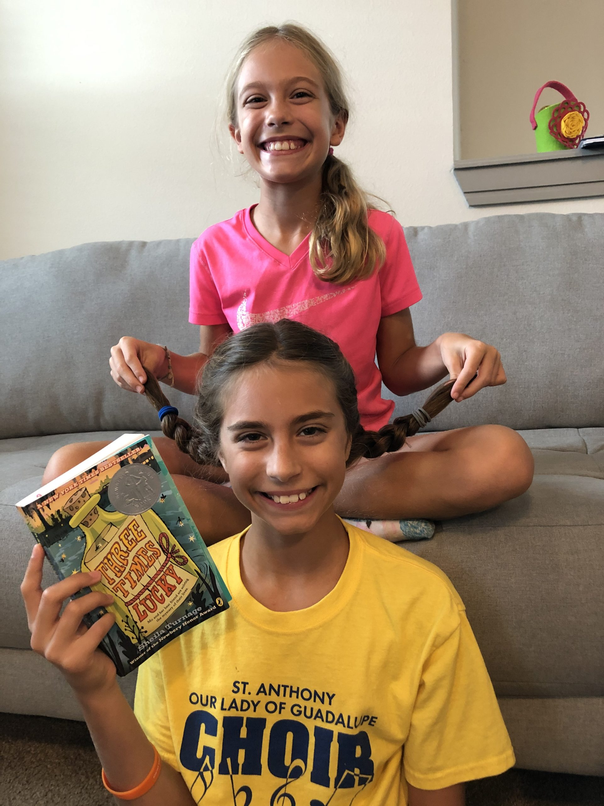 2 kids, girls, holding up the Three Times Lucky book, smiling at the camera.