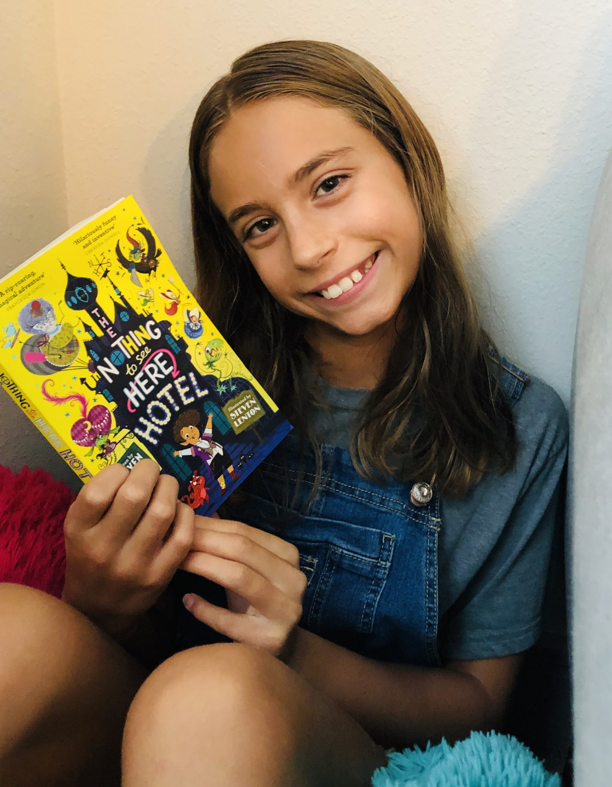 Kinley holding the book , The Nothing to see Here Hotel by Steven Butler for the the Children's Book Review.