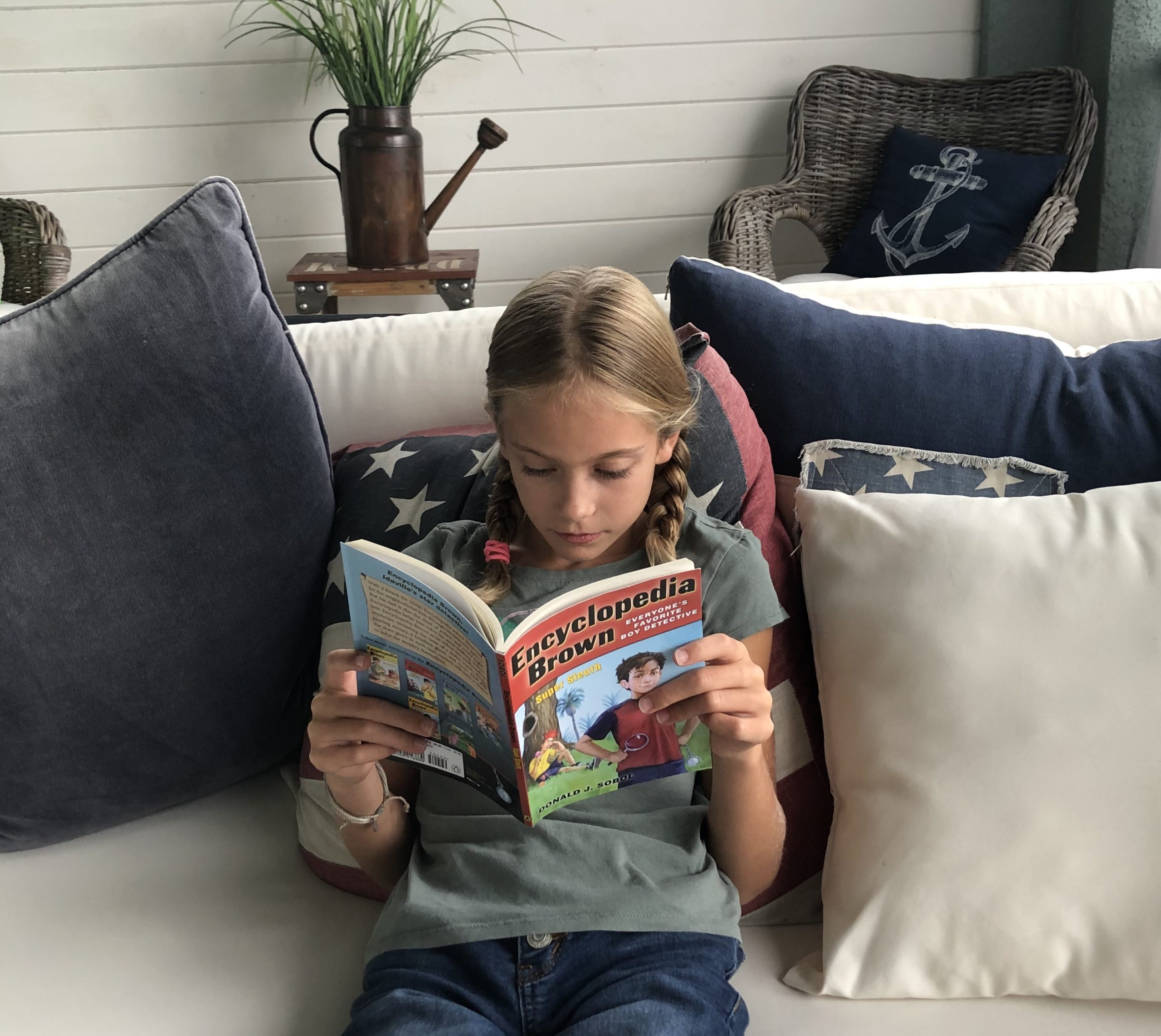 Brecken reading Encyclopedia Brown Super Sleuth for a children's book review.
