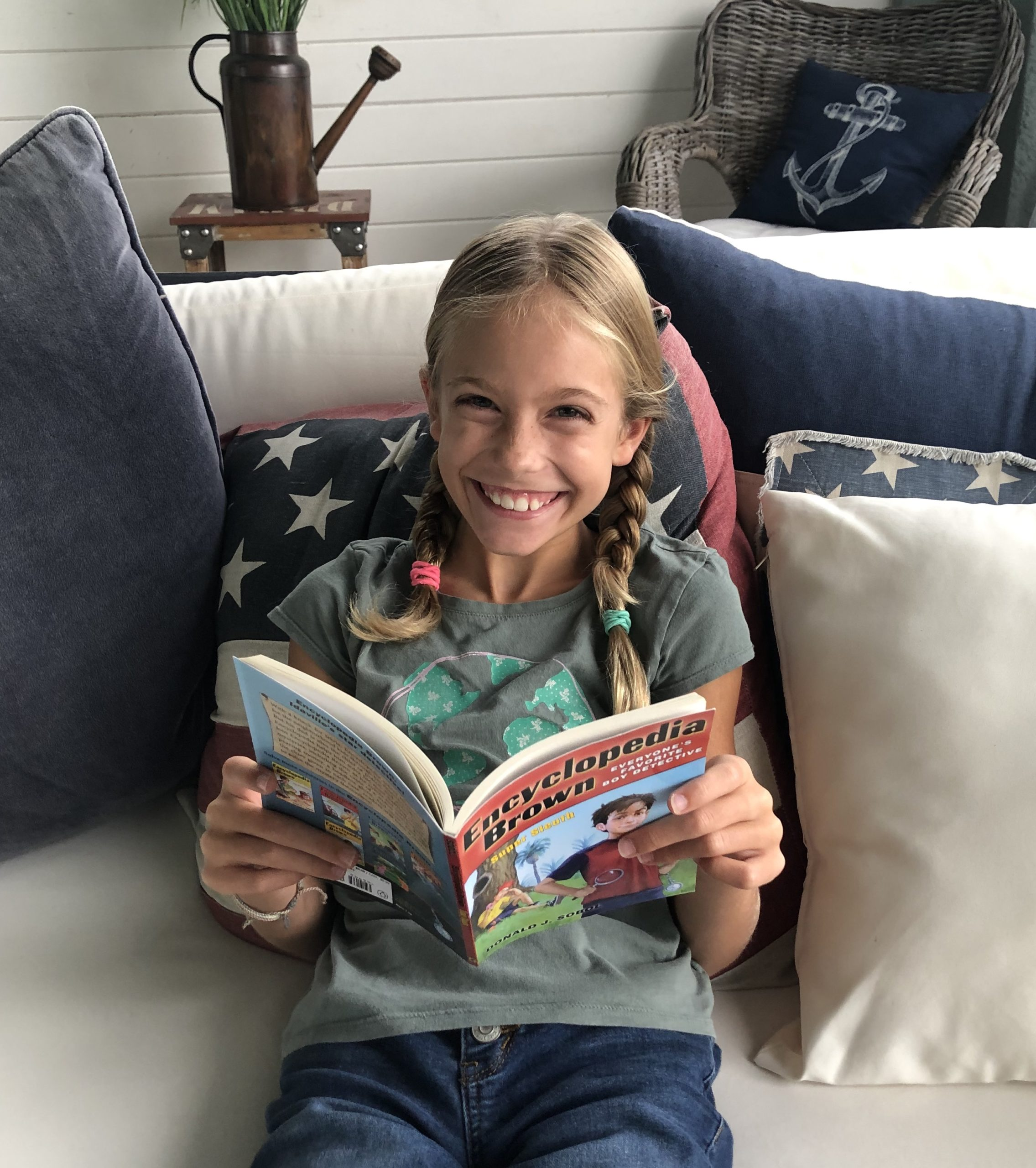 Blonde Brecken smiling and reading Encyclopedia Brown's Super Sleuth book.
