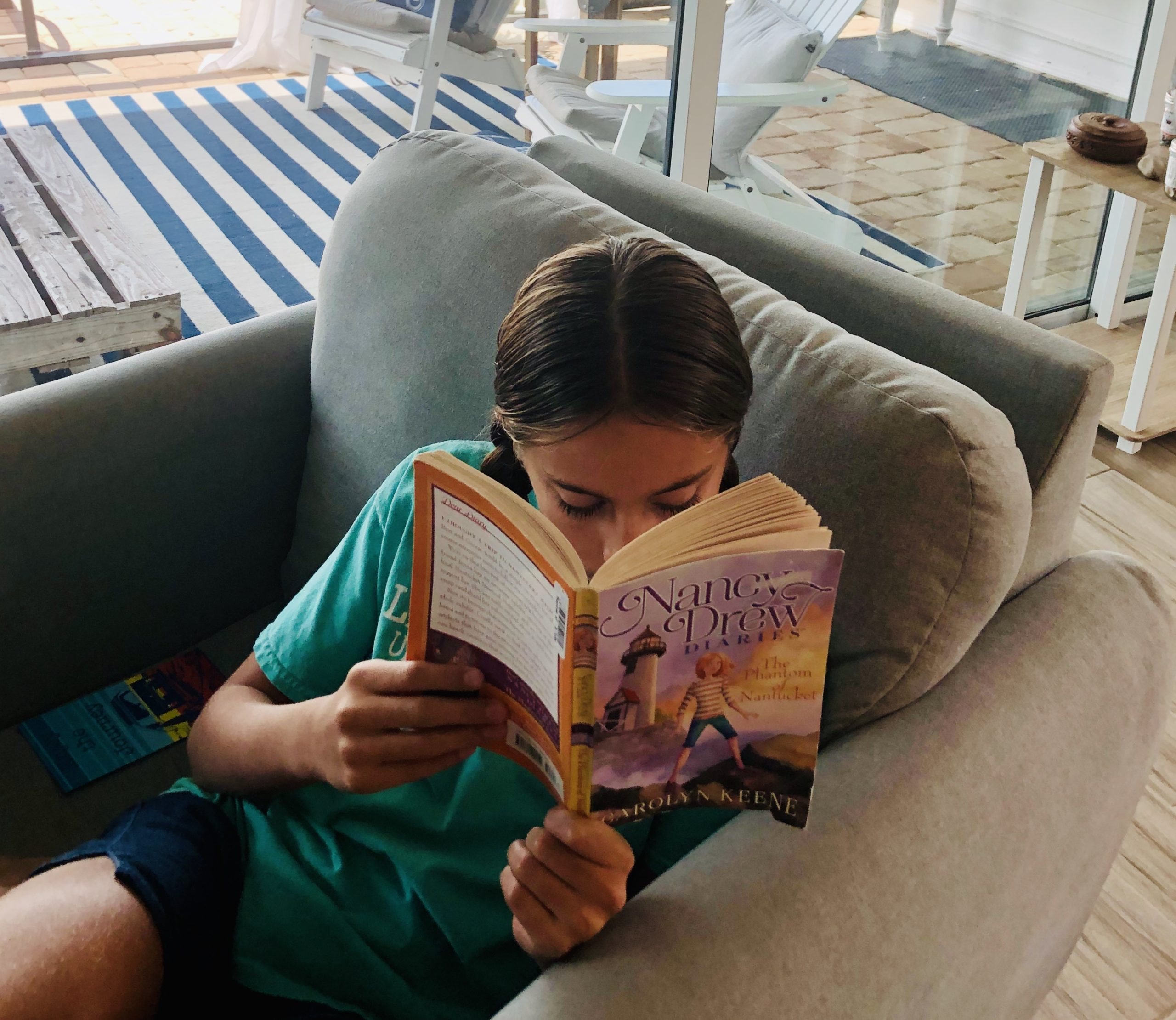 Kinley, 11 year old girl, reading Nancy Drew's Phantom of Nantucket. She's sitting in a chair with her head down.