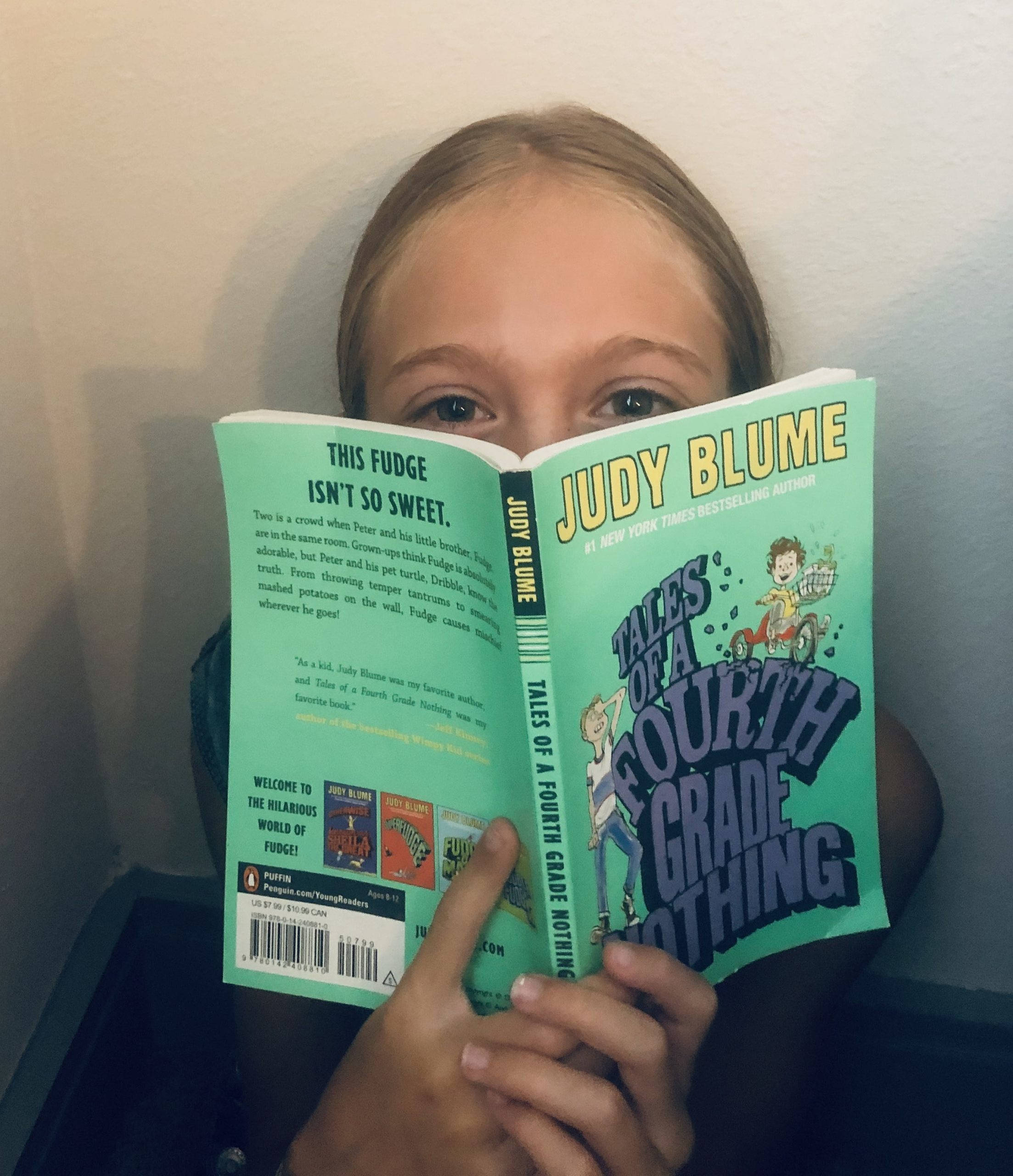 Brecken peeking over the book, Tales of a Fourth Grade Nothing by Judy Blume for the children's book review.