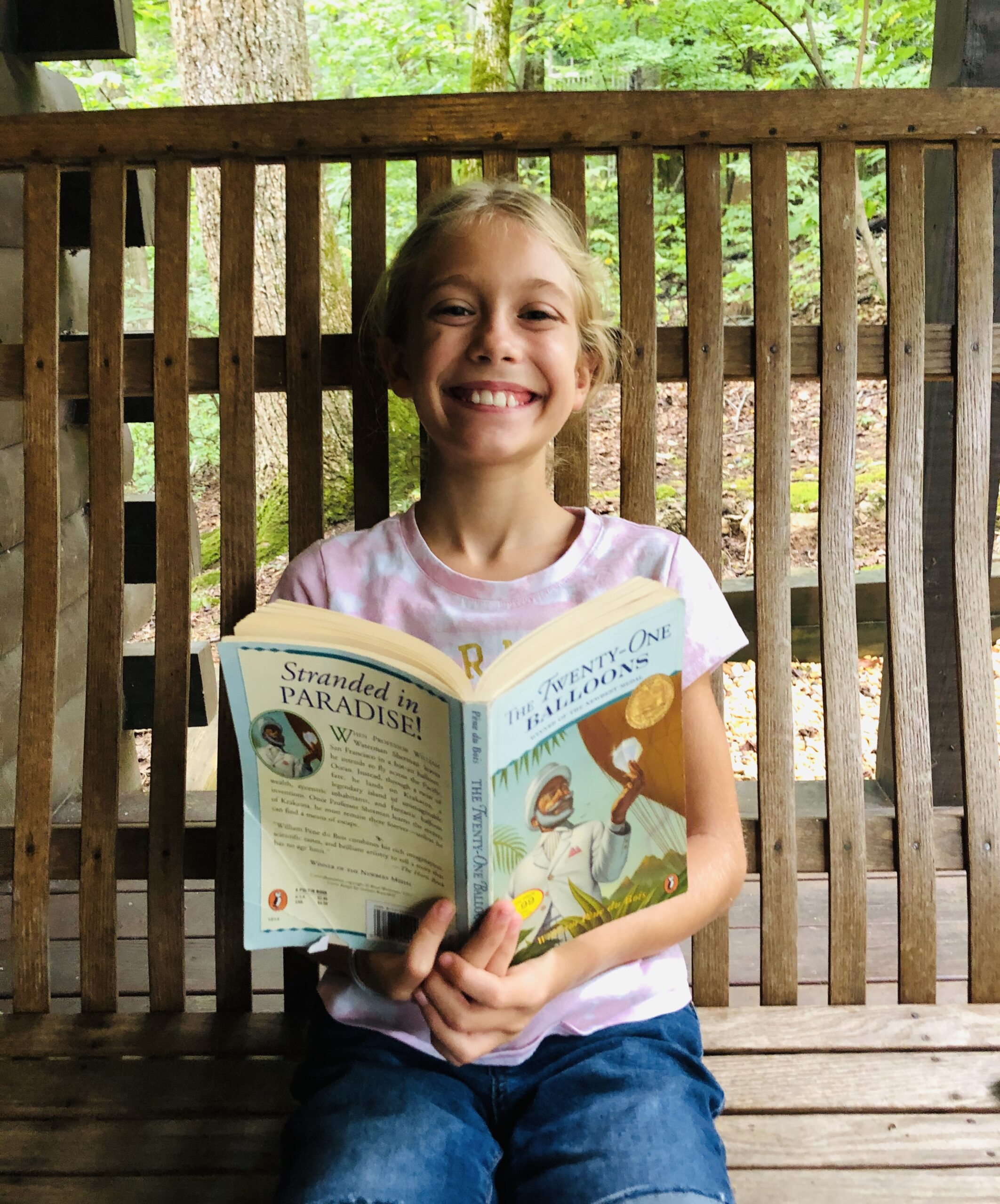 Blond haired Brecken sitting in a swing reading Twenty One Balloons for the Children's Book Review.