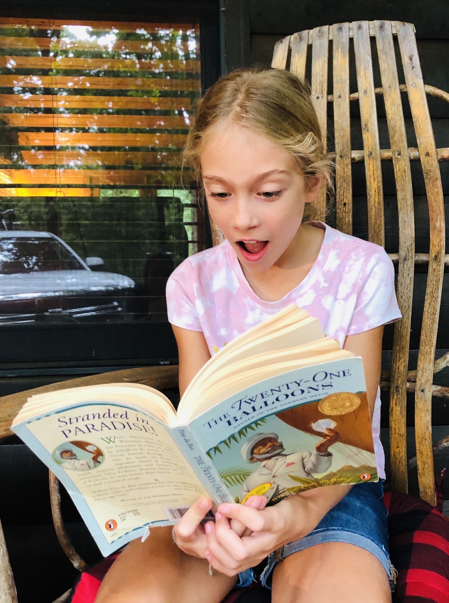 Girl reading with mouth open, like she's surprised, for the Children's Book Review on Twenty-One Balloons.