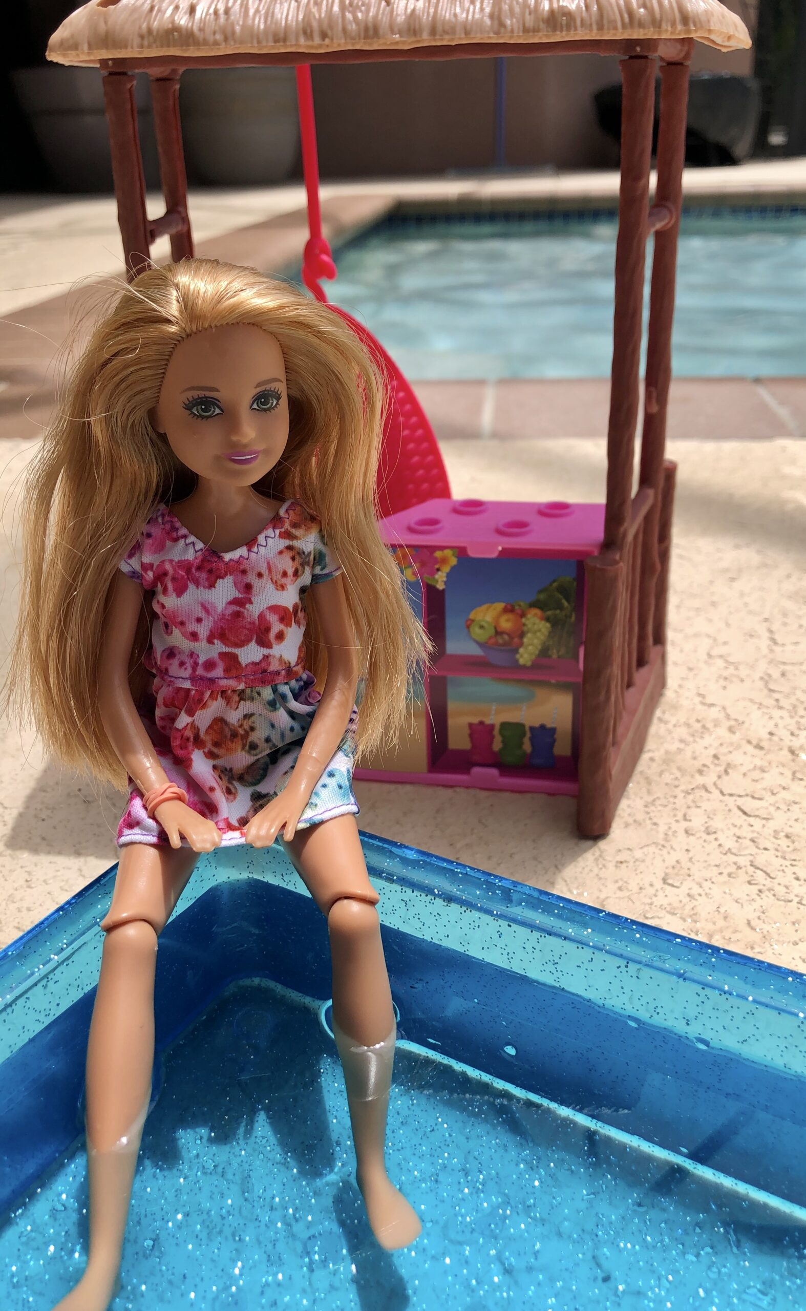 A Stacie Doll sitting with her legs in a pool.