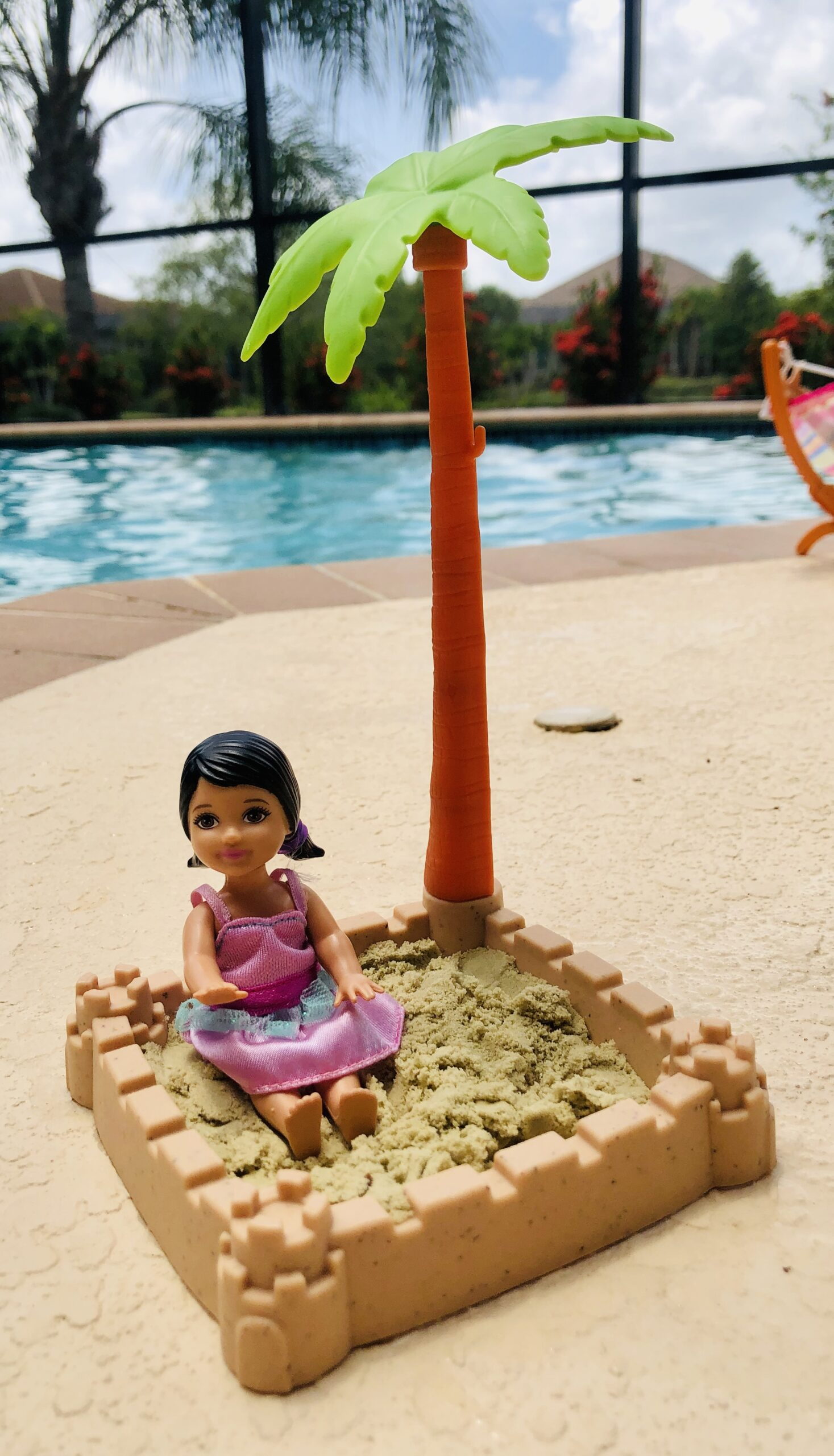 A Baby Barbie Doll in a sandbox. It has a palm tree and real sand in it. It's for the Barbie Doll Story, Goodbye Costa Rica.