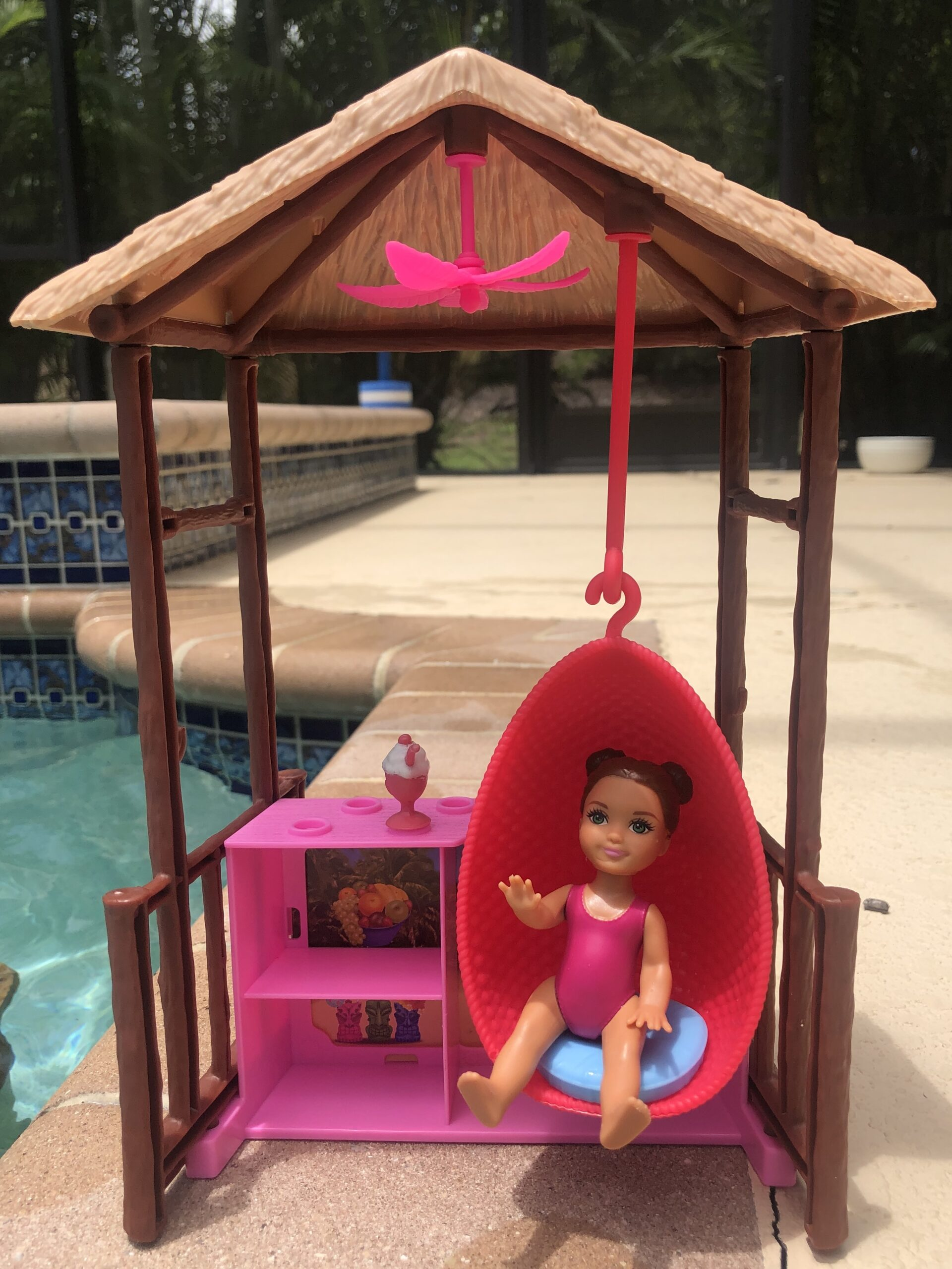 A baby Barbie Doll sitting in a swinging chair outside for the Barbie Doll Story.