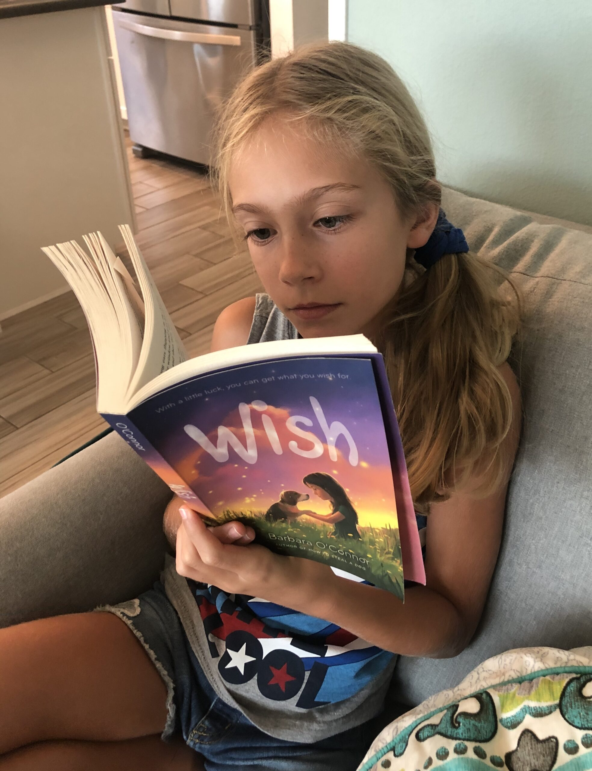 Blonde haired Brecken reading Wish by Barbara O'Connor for the children's book review.