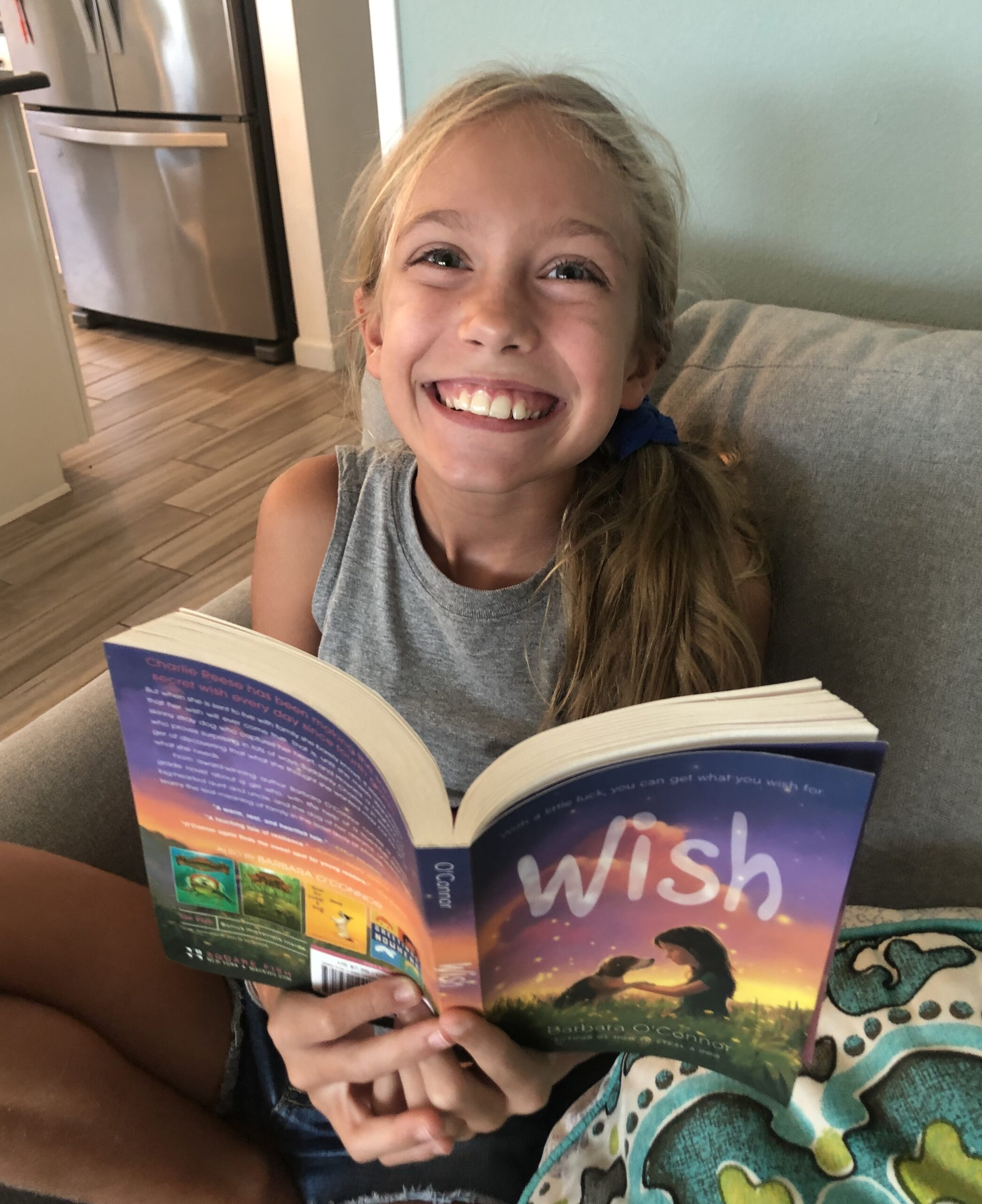 Blond haired girl reading Wish for the children's book review on it.