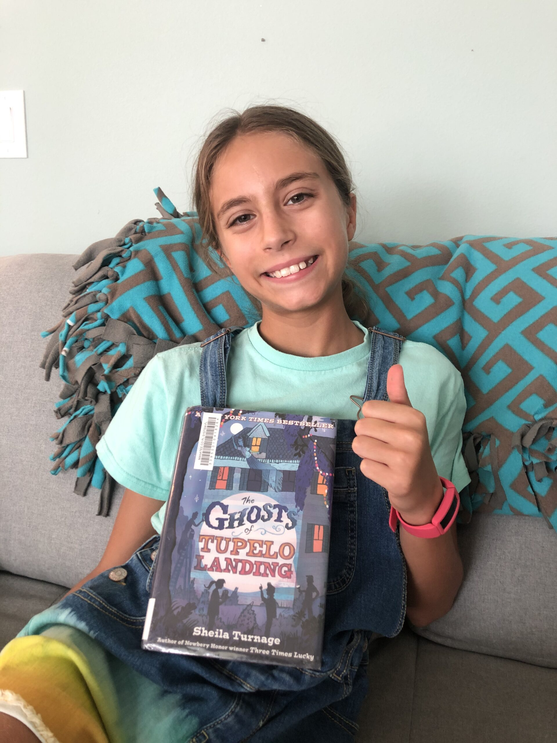 Kinley giving a things up while holding the book of The Ghosts of Tupelo Landing for the children's book review.