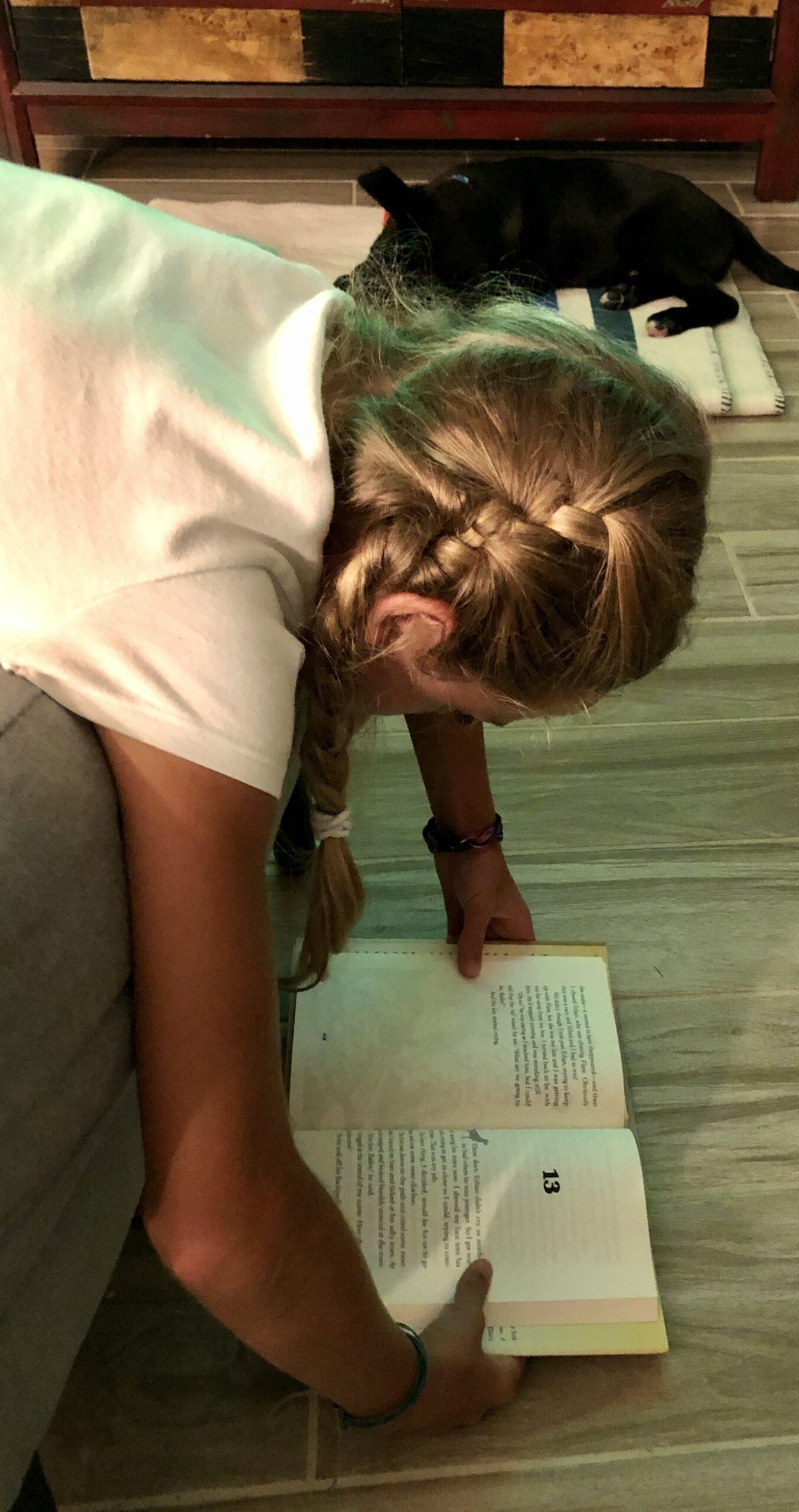 Girl reading Bailey's Story for the Book Review. She's hanging over a chair with the book on the floor.