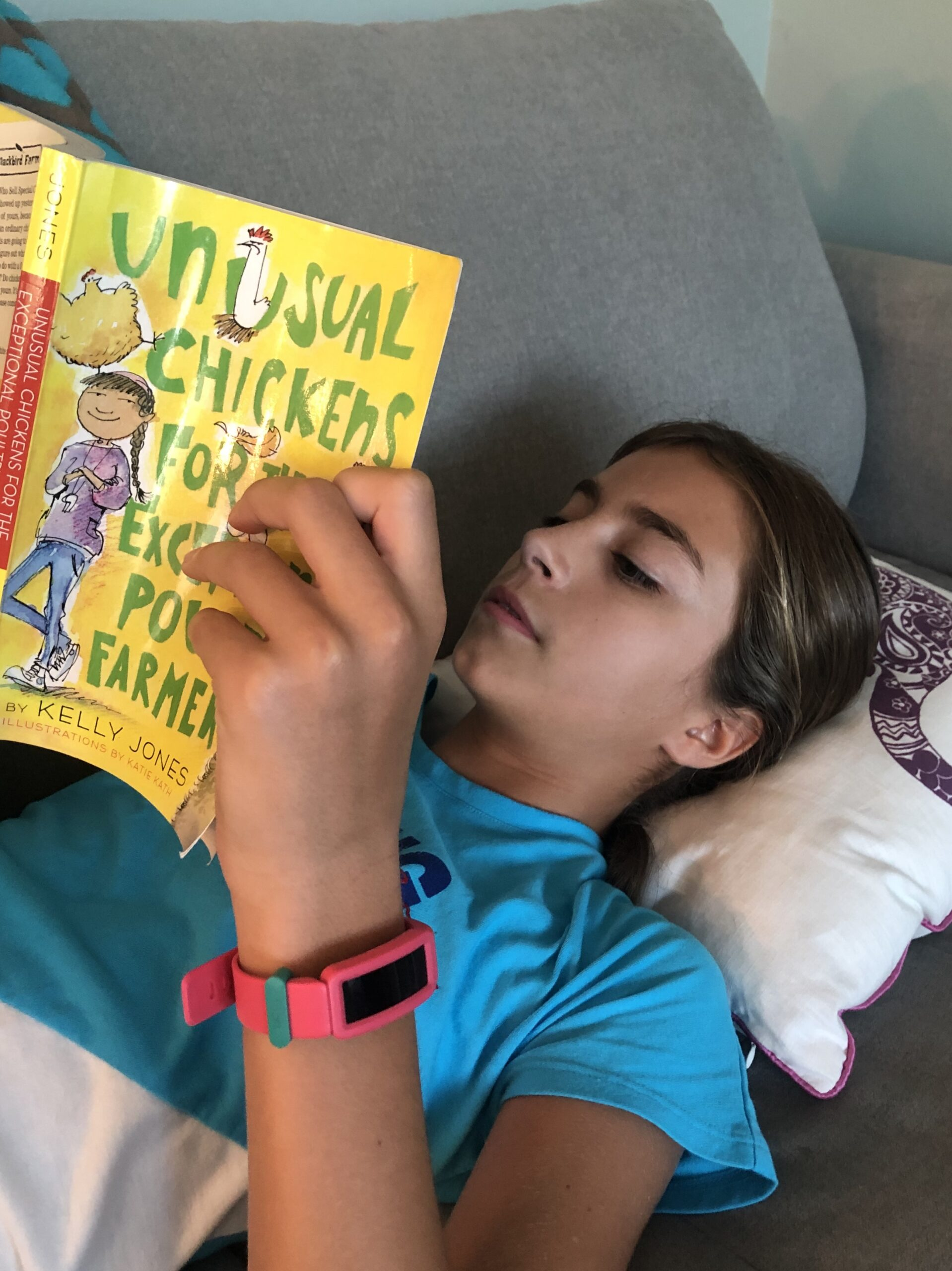 Girl laying down and reading Unusual Chickens for the Exceptional Poultry Farmer for the book review.