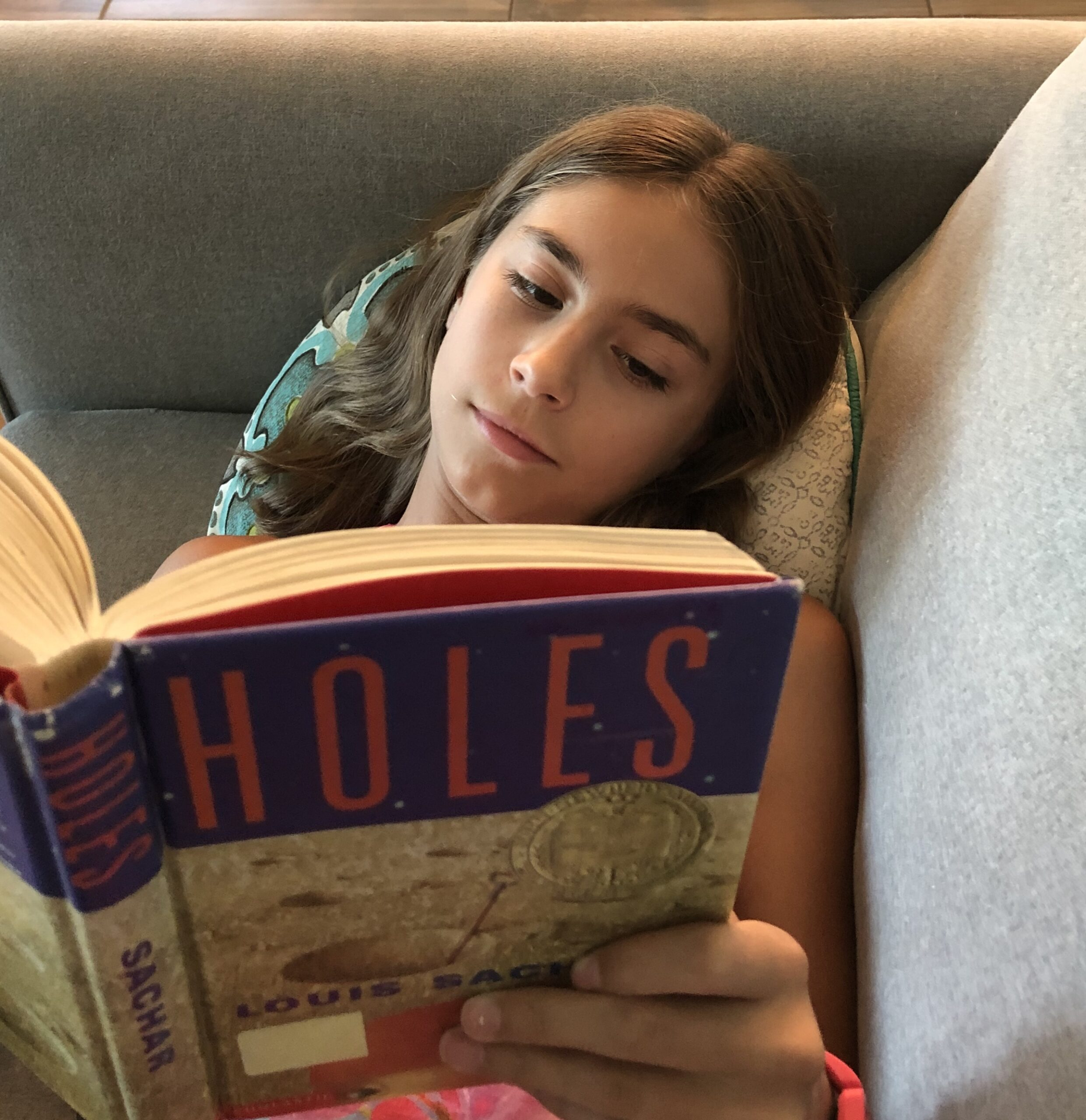 A girl laying on the couch reading Holes by Louis Sachar.