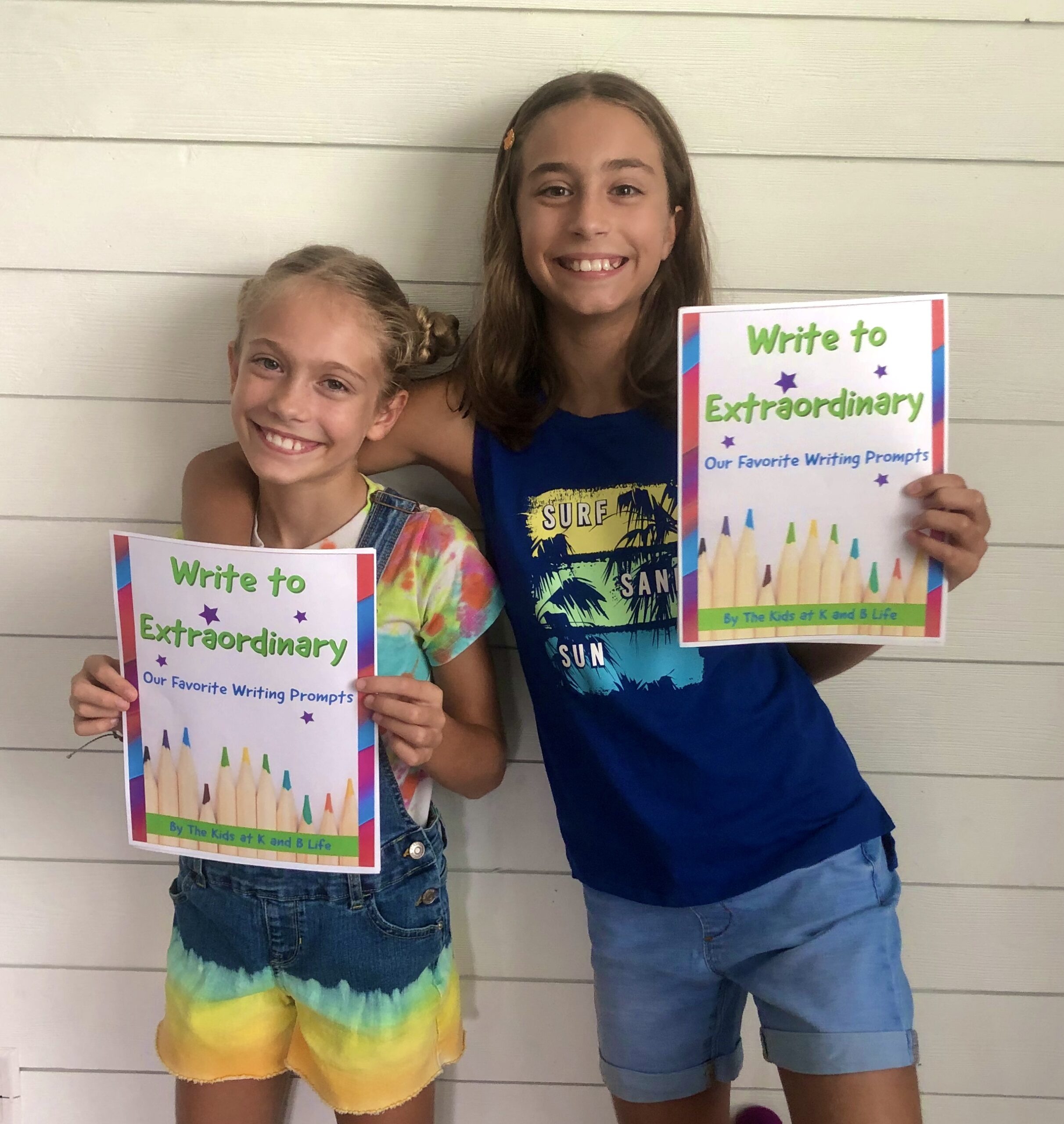 K and B holding up the Write to Extraordinary Guide for writing prompts and tips.