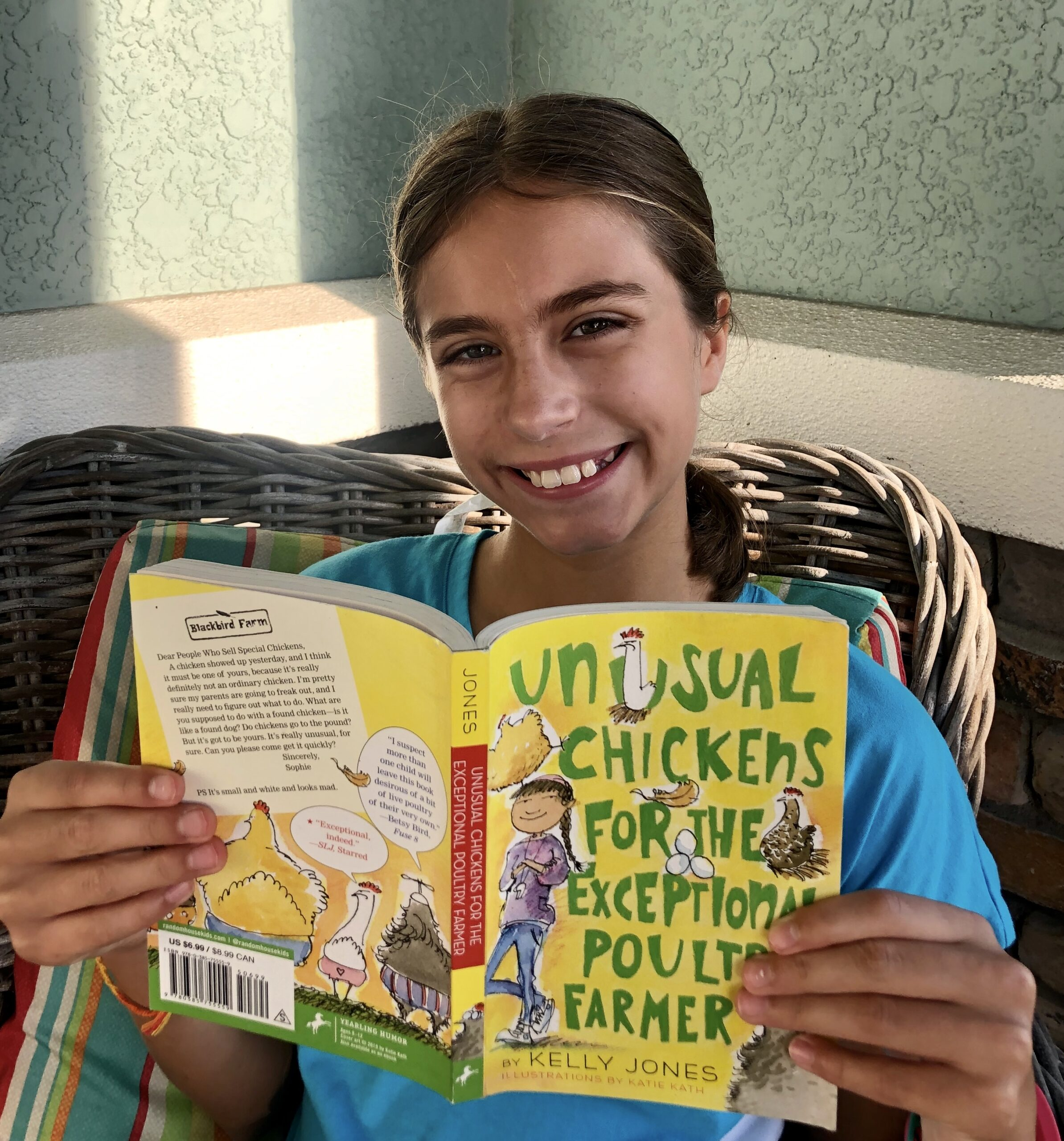 Girl smiling while reading Unusual chickens for the Exceptional Poultry Farmer for this book review.