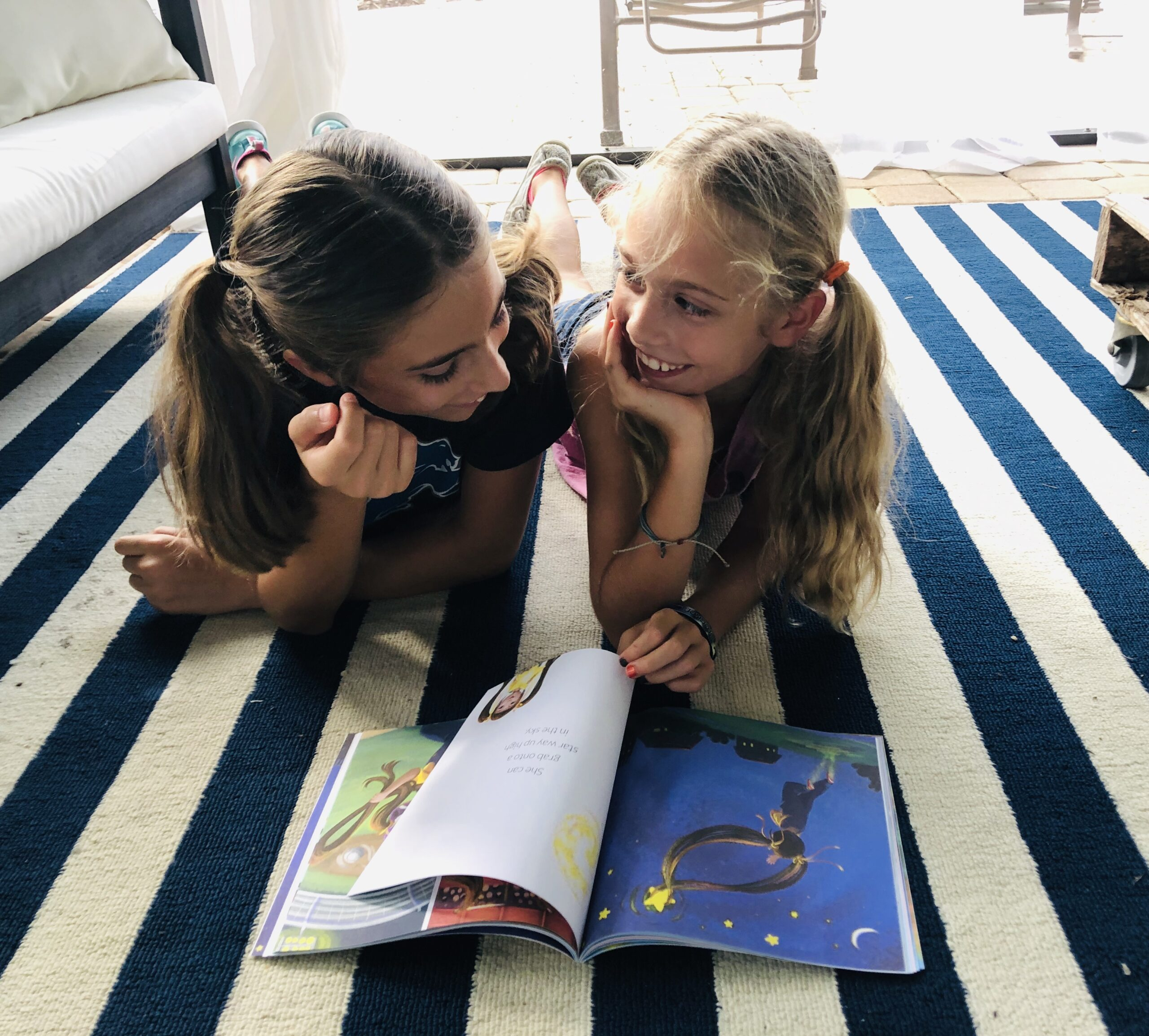 2 girls reading a book, smiling.
