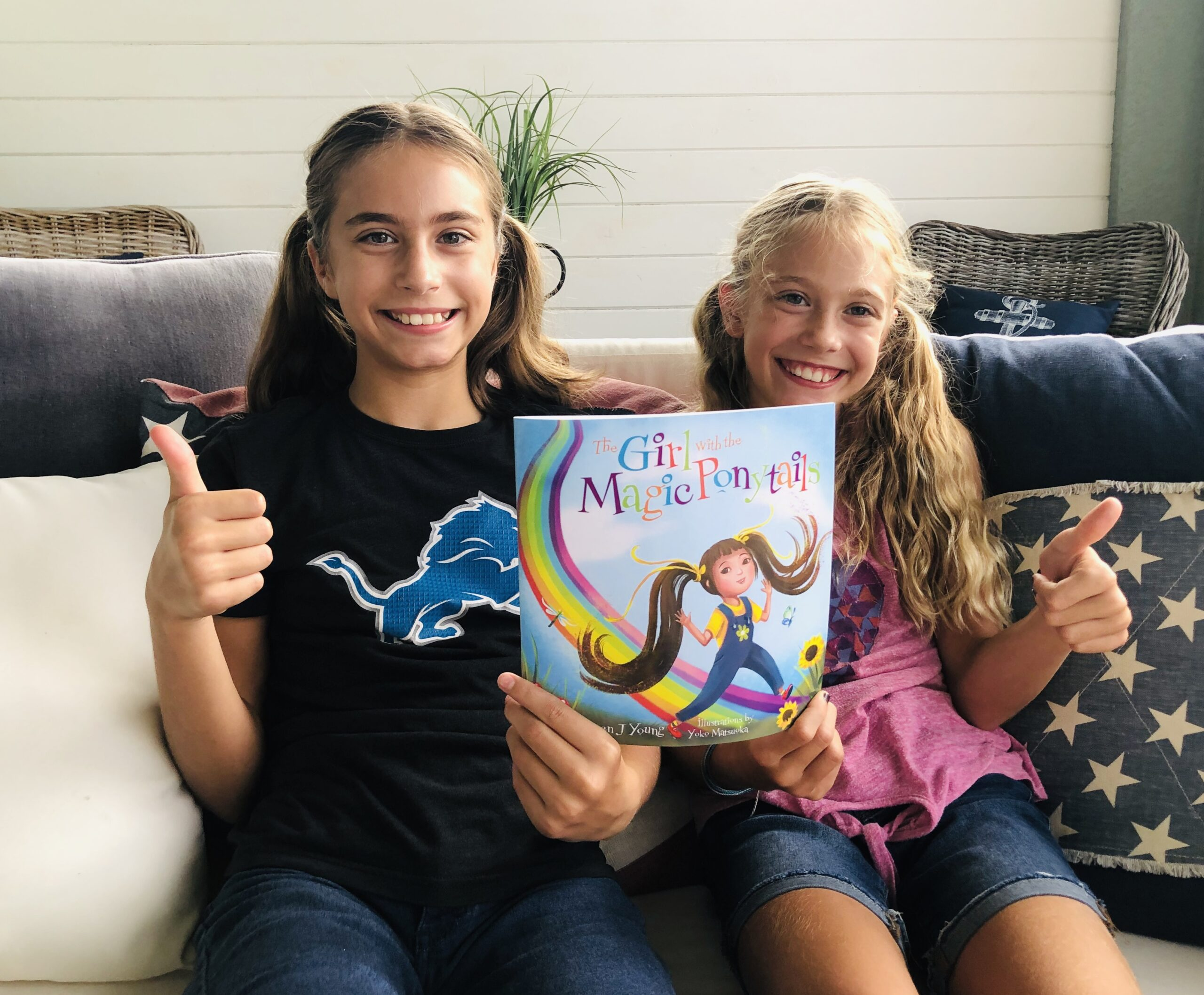 2 girls giving a thumbs up for a children's book review on The Girl with the Magic Ponytails.