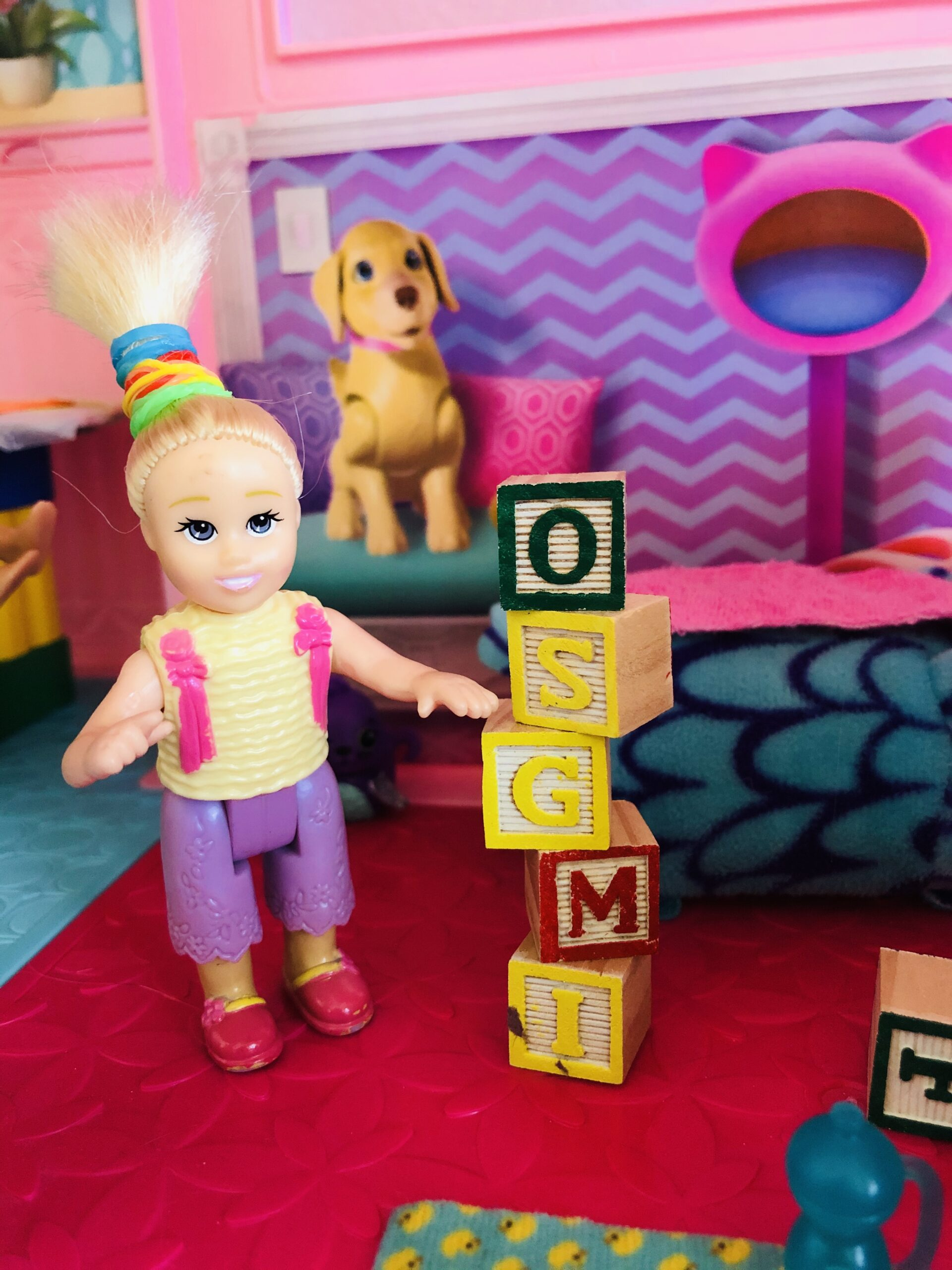 A little doll playing with blocks in the Barbie Dreamhouse.