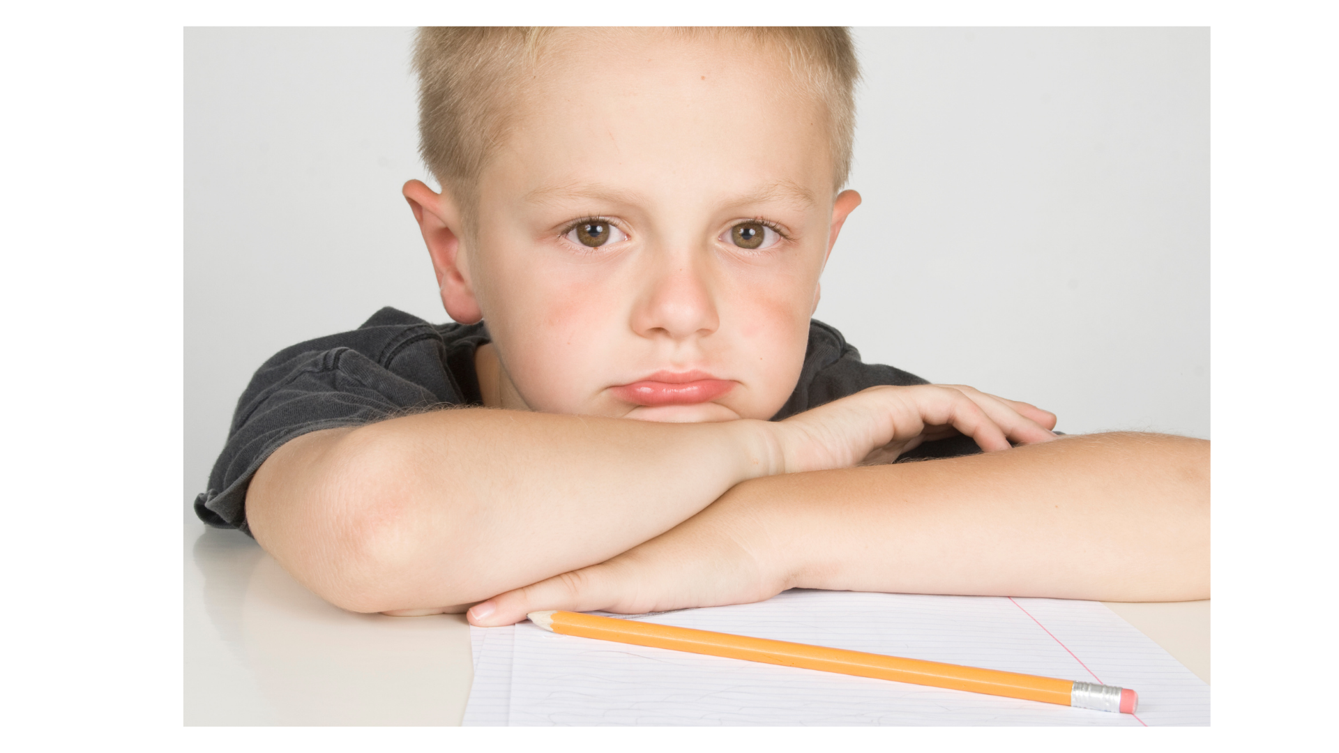 Unhappy kid with pencil and paper. Looks like he hates writing.