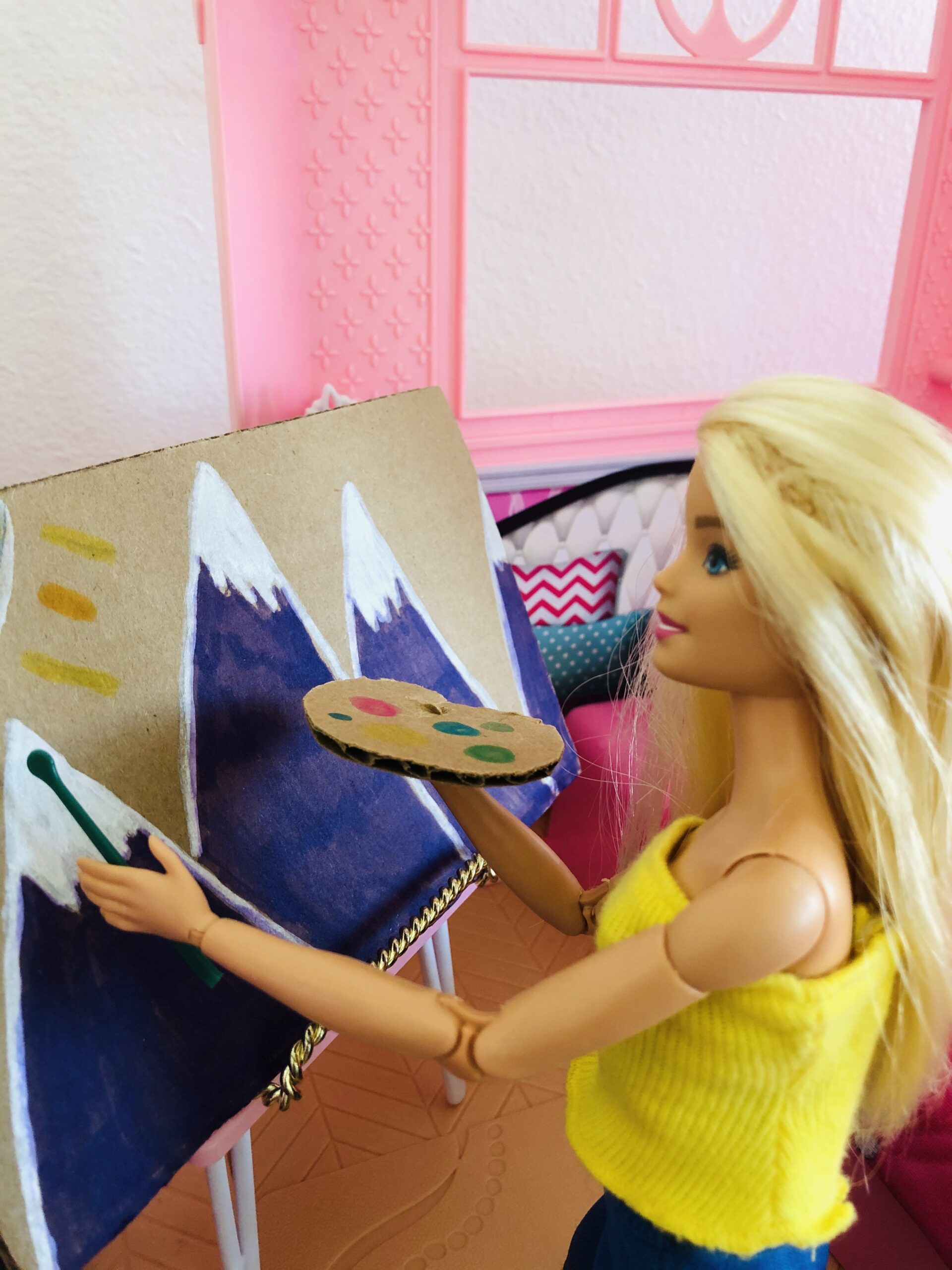 Barbie painting a mural of mountains.
