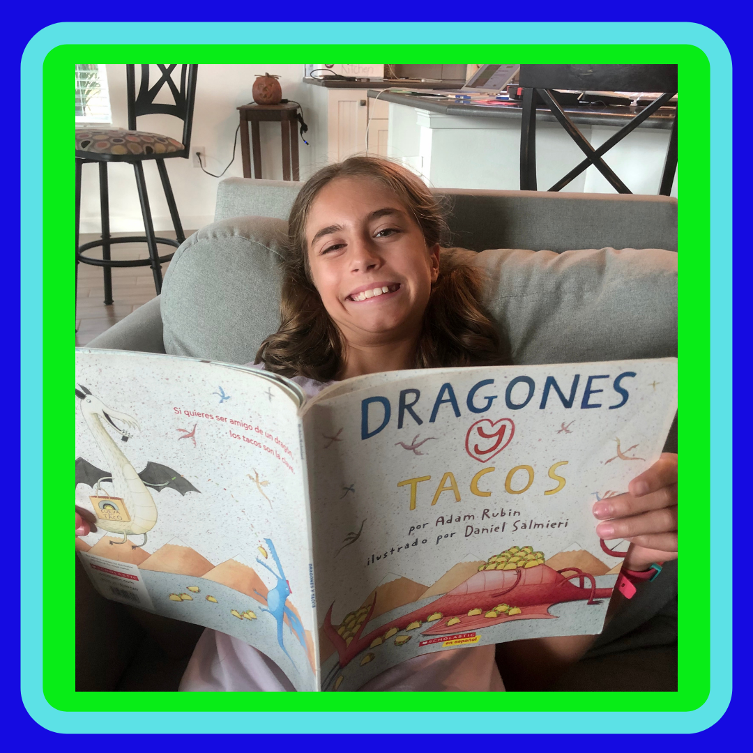 A girl reading Dragones y tacos or Dragons love Tacos for the children's book review.