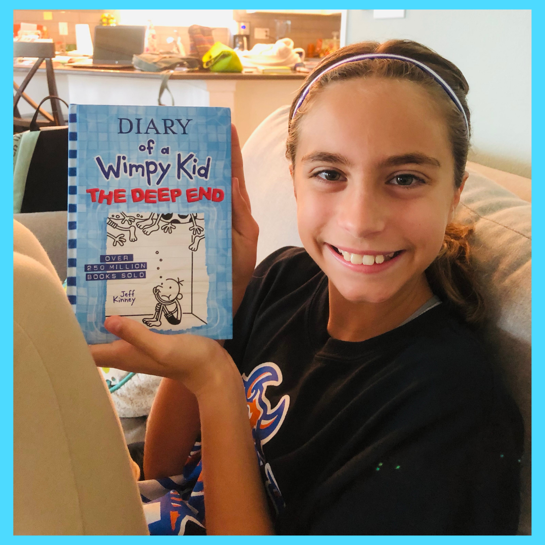 Girl holding up a Diary of Wimpy Kid Book for the Book Review on the Diary of a Wimpy Kid Series.
