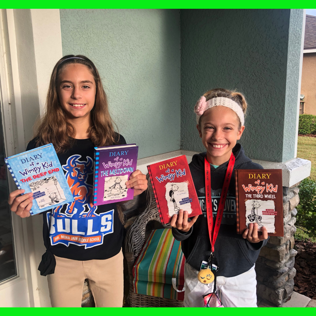 2 girls holding Diary of a Wimpy Kid Books.