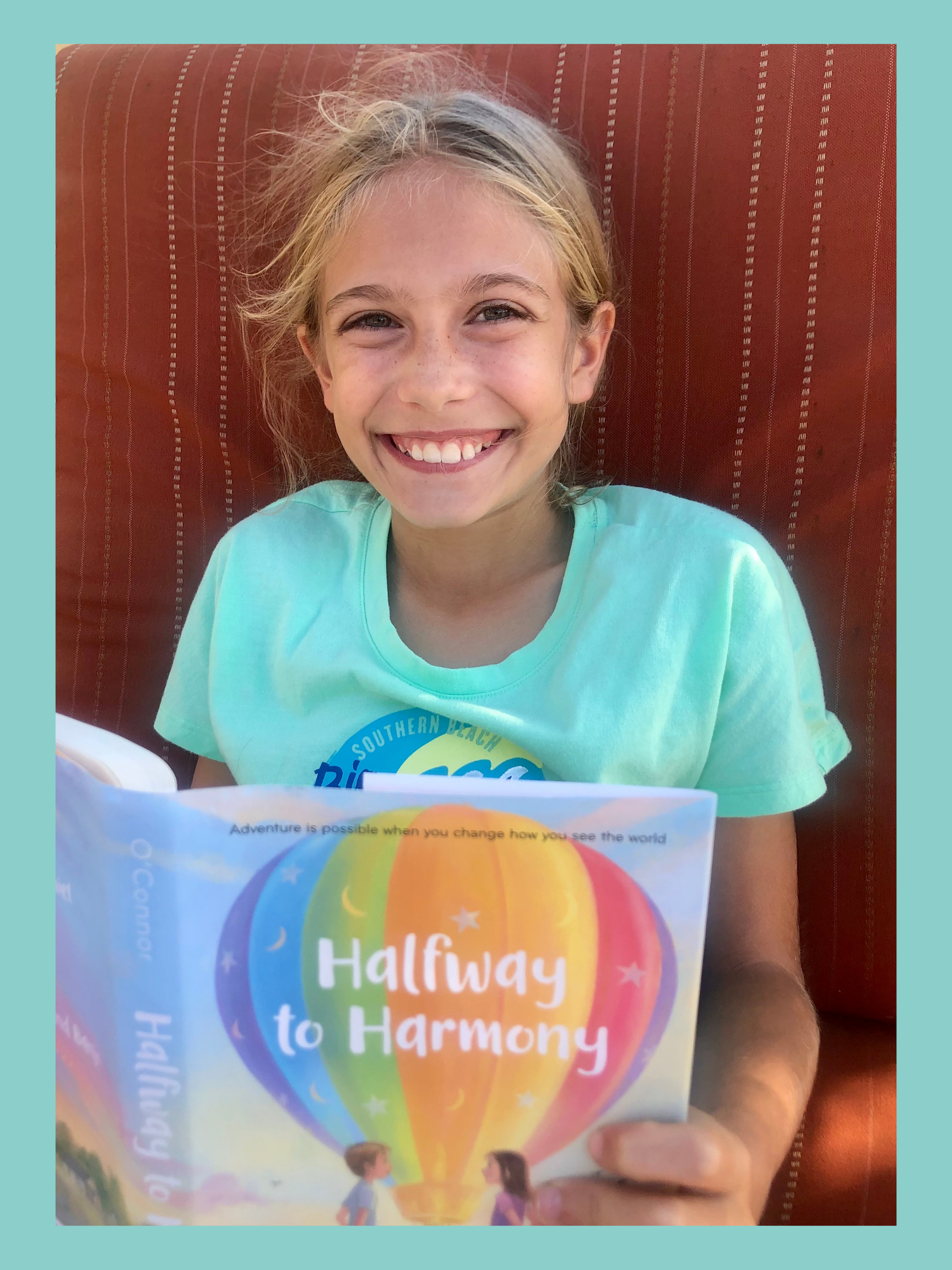 Girl smiling up while reading Halfway to Harmony. It's for the Kids Book Review.