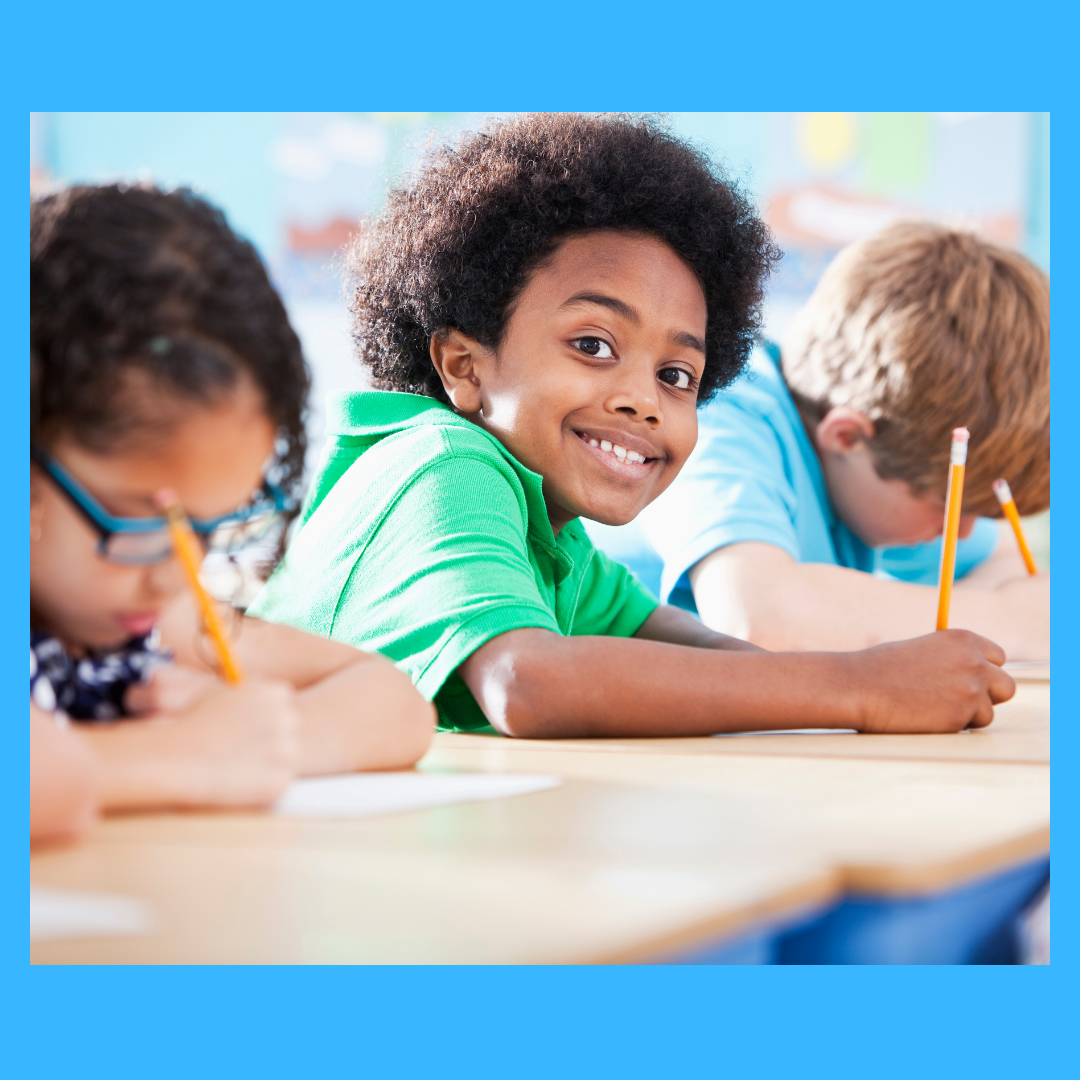 A kid in a classroom looking happy while writing.